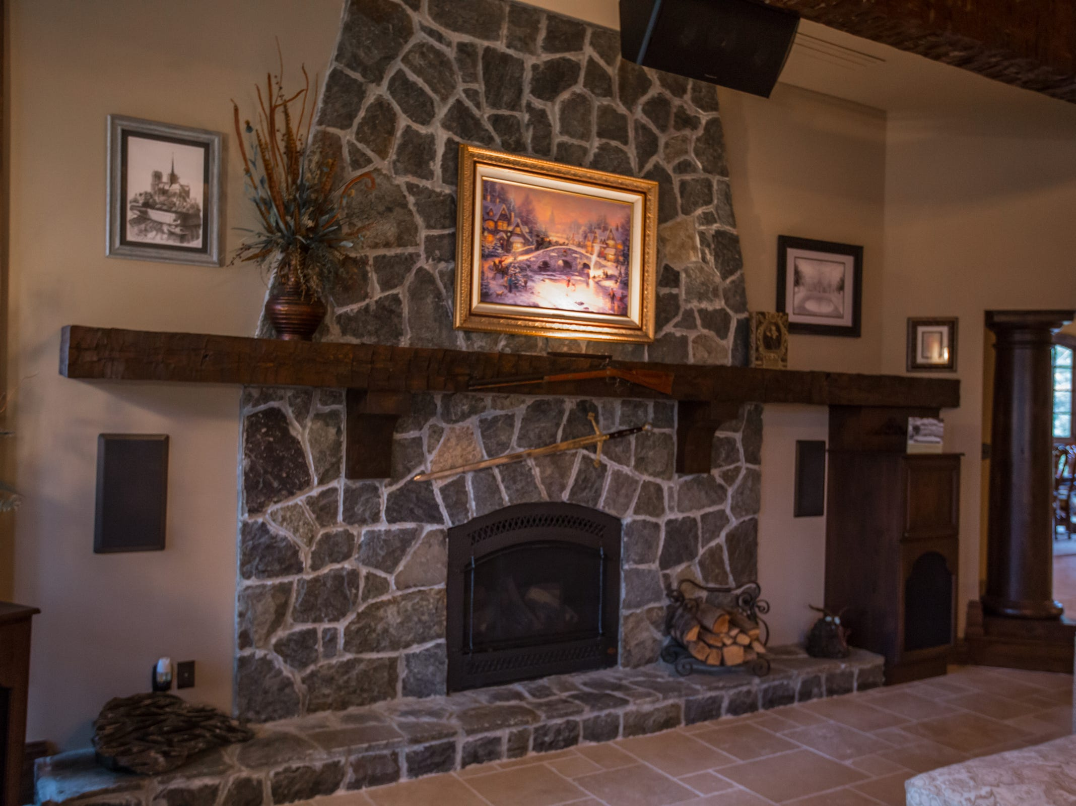 A natural stone fireplace in the great room of the home envisioned after the Biltmore Estate designed by Alex Bogarts and built by an award winning builder as his own personal residence.