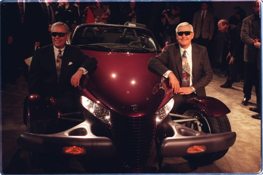 "Bob Eaton (left), president, and Bob Lutz, chairman of Chrysler pose for the cameras after unveiling the Prowler, a concept roadster meant to change Plymouth's outdated image to a more ""hip"" one."
