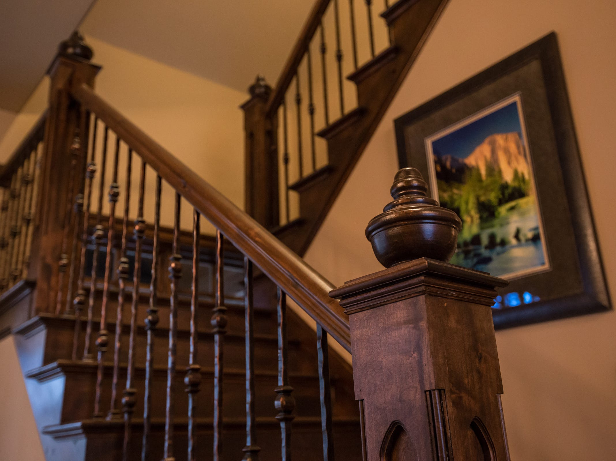 Stained alder wood staircase with hand forged wrought iron of a dining area in the custom designed kitchen.