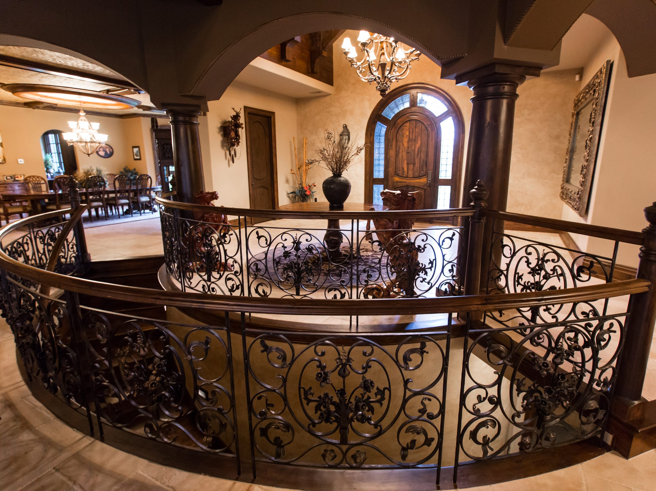 The large foyer includes arches, pillars, seeded glass, intricate wrought iron and Venetian plaster, garnished with two sculpted stallions.