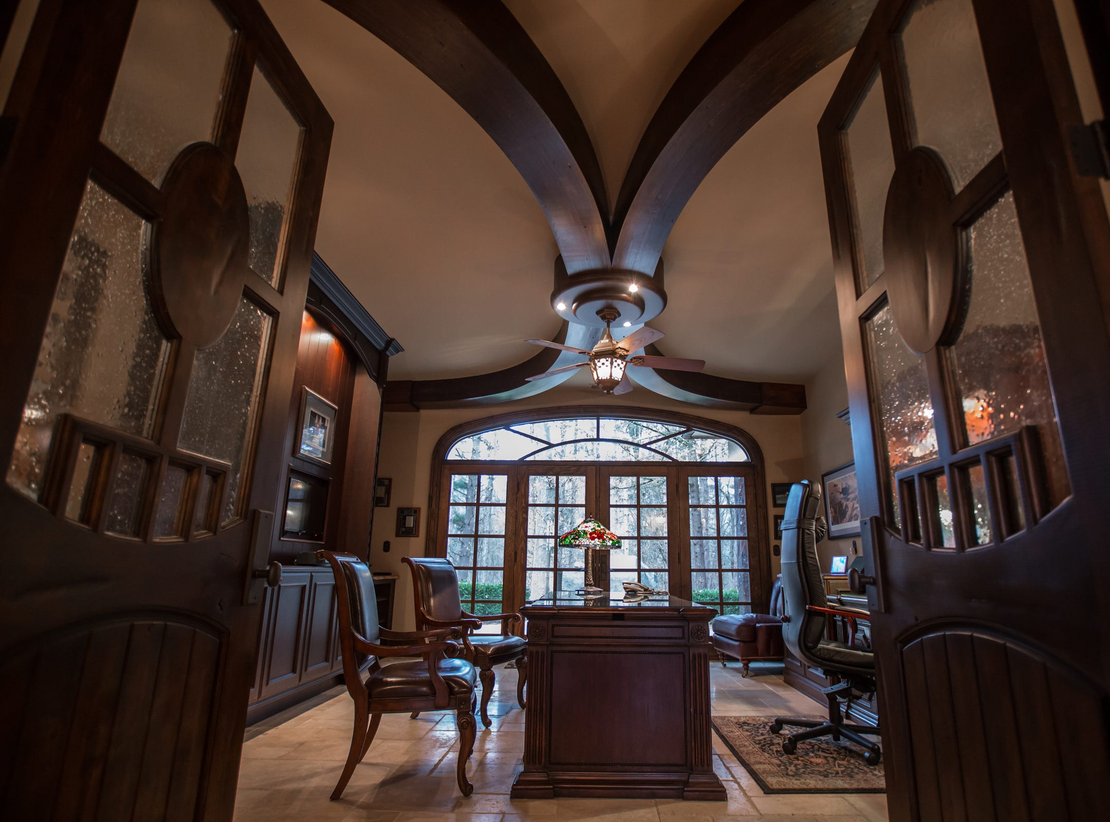Unique radius-curved beams in the ceiling, carved alder doors and beautiful French doors are seen in the home envisioned after the Biltmore Estate designed by Alex Bogarts and built by an award winning builder as his own personal residence.