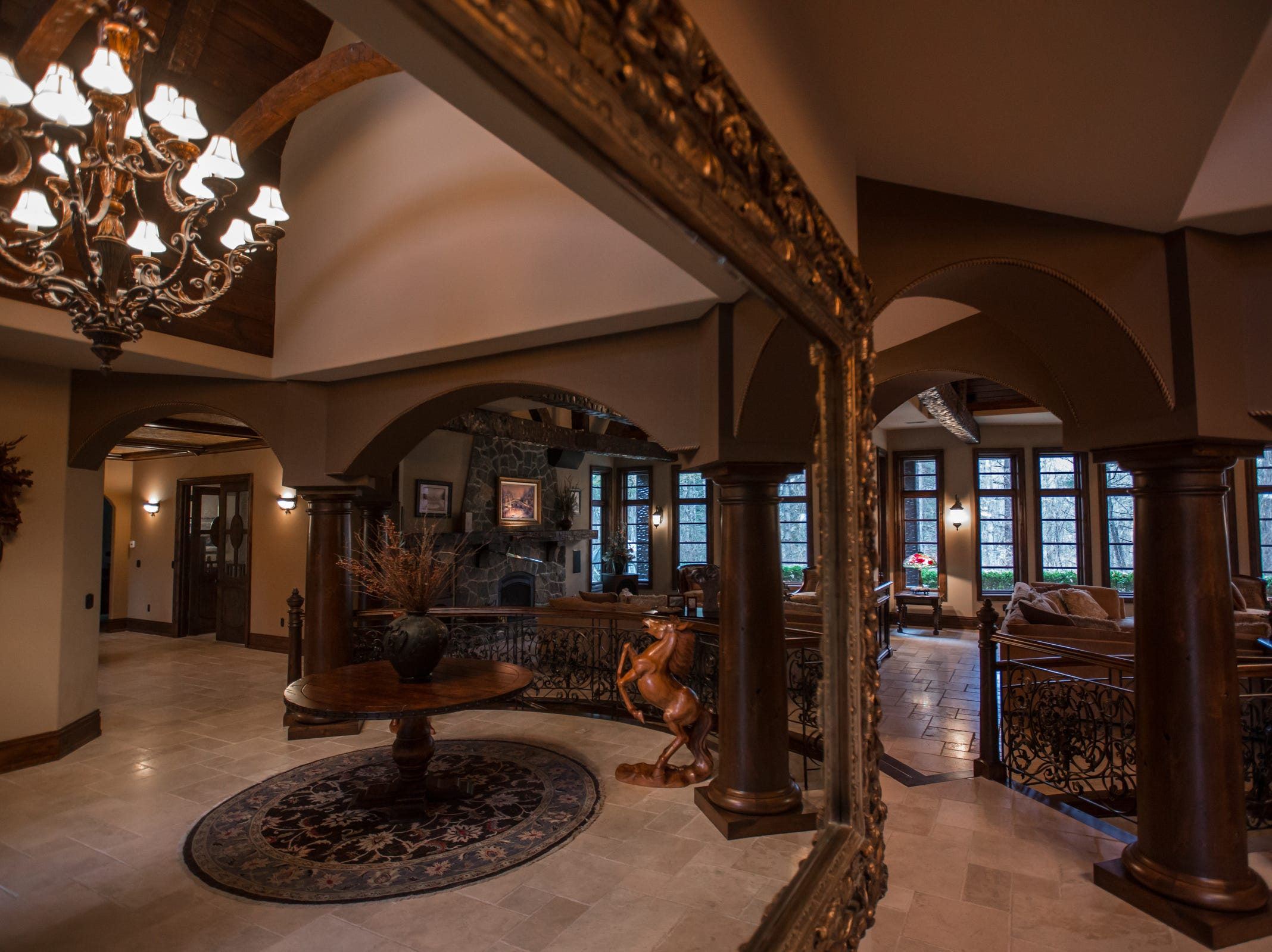A large mirror in the foyer reflects the great room of the home envisioned after the Biltmore Estate designed by Alex Bogarts and built by an award winning builder as his own personal residence.
