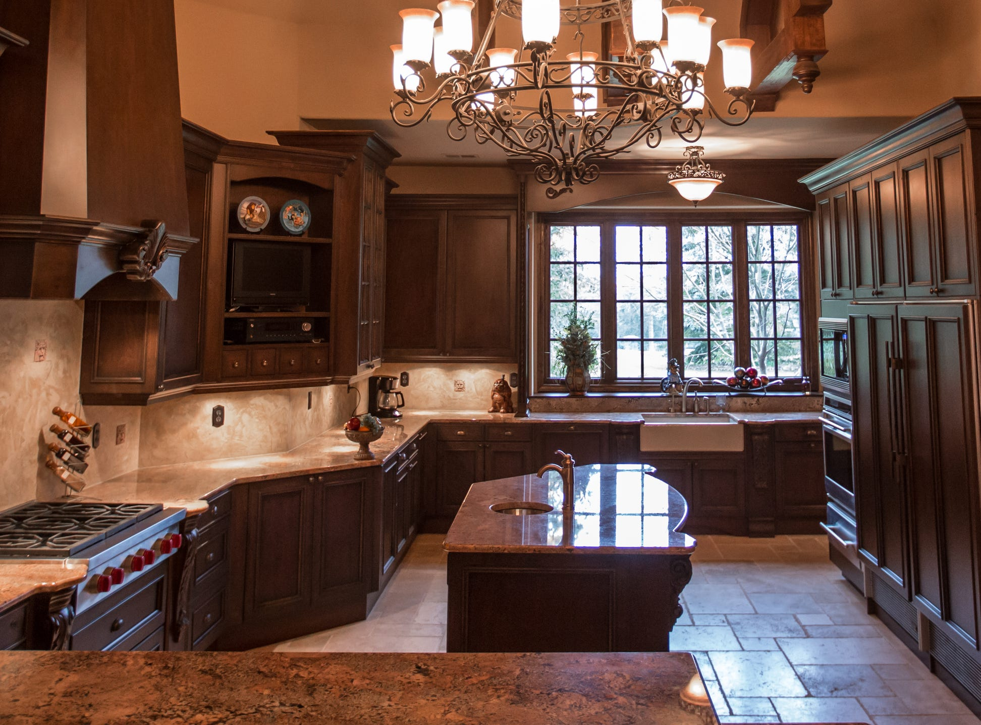 A view of the custom designed kitchen with professional grade appliances and natural limestone tile imported from Italy.