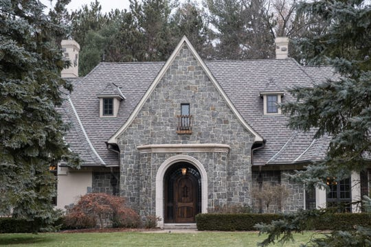 Blue mountain granite covers a steep-peaked French style house that's built on 5 acres cut into the side of Stoney Creek Metropark. The whole five acres is wrapped in a decorative iron fence.