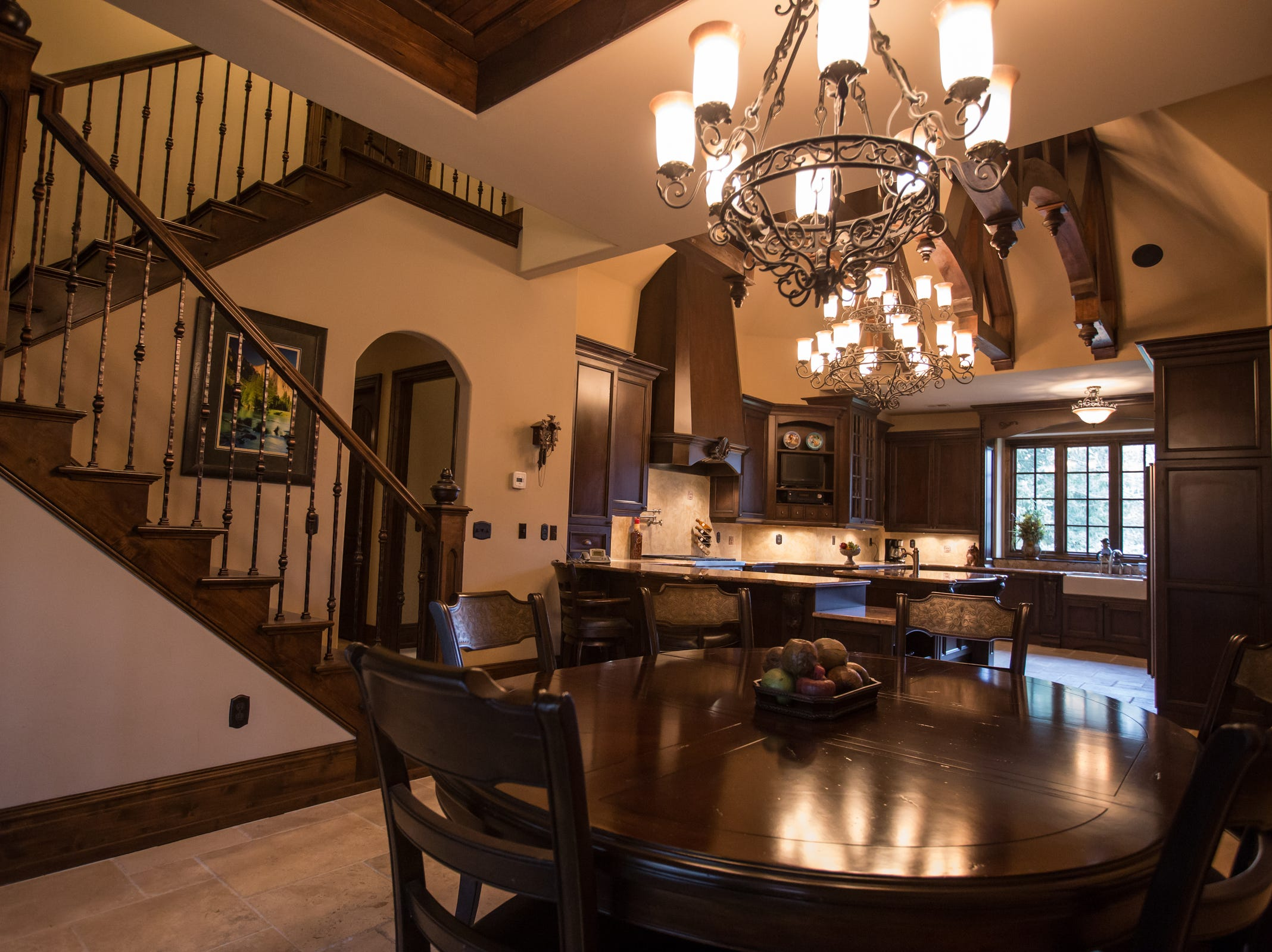 Casual eating is next to the kitchen, with a raised wood ceiling and chandelier. As finished, the house is all one level, but the staircase at left leads to a framed-in second floor area that can be made into more rooms.