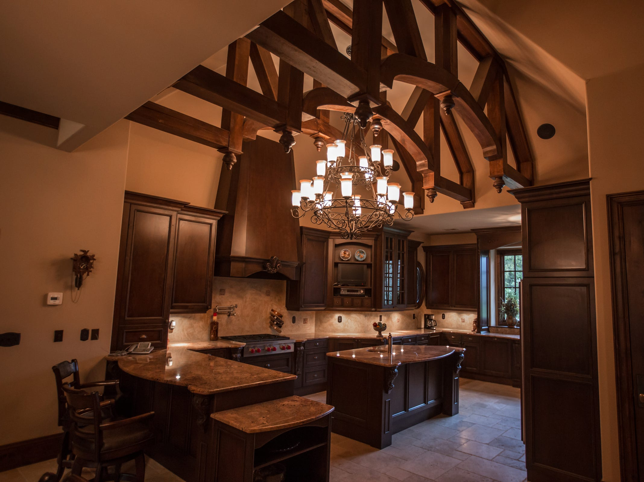 The kitchen ceiling is raised under one of the roof peaks, and filled with a pattern made of beams. Appliances are Wolf, Sub-Zero, Bosch.