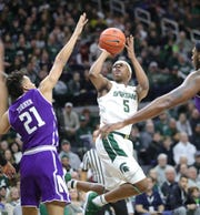 Michigan State guard Cassius Winston scores against Northwestern guard A.J. Turner during first half action Wednesday, January 2, 2019 at the Breslin Center in East Lansing, Mich.