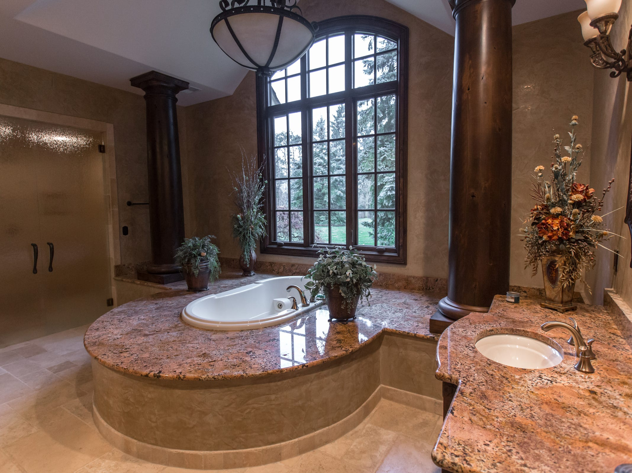 A lavish bath repeats the thick alder pillars in the foyer while the floors are Italian limestone, heated by hot water below.