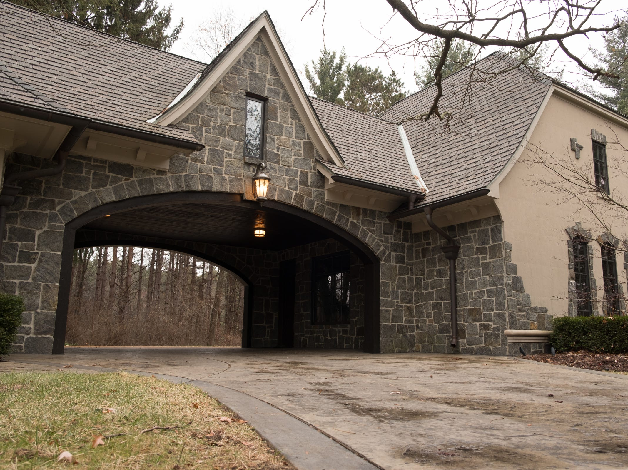 The garage portico leads to heated parking for six to eight cars, including a stone covered barn. The area over the garages has been framed in but not finished, so it can be turned into more rooms by the new owner. The home sets back into the exterior boundary line of Stoney Creek Metro Park.
