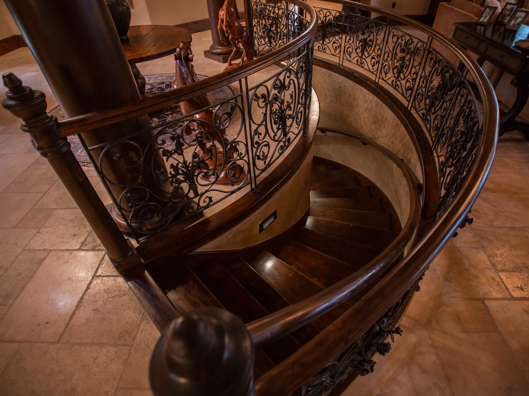 Hand forged wrought iron and adler wood staircase leading to the basement.