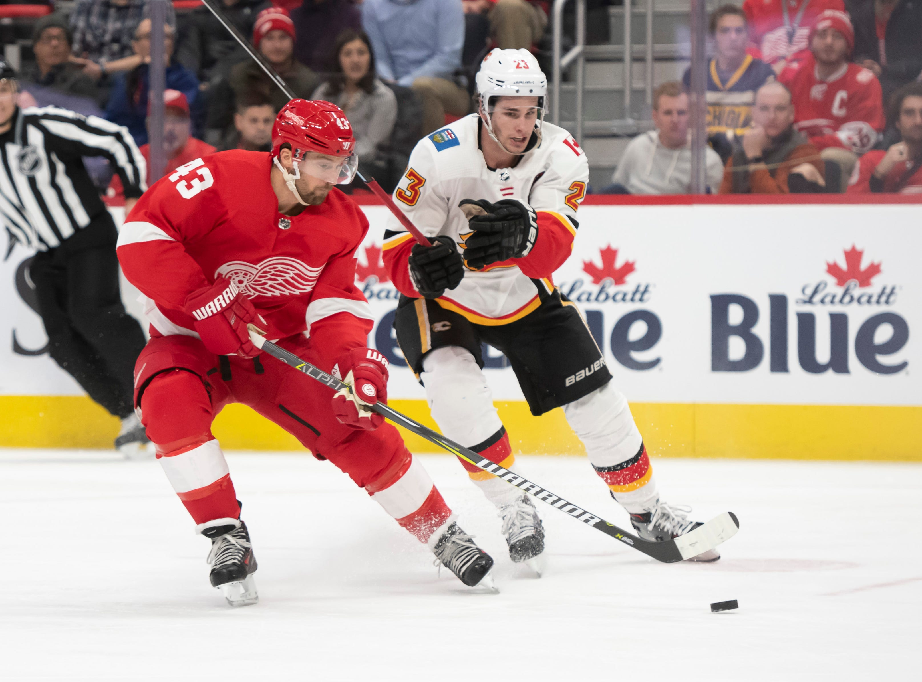 Detroit center Darren Helm keeps the puck away from Calgary center Sean Monahan in the third period.