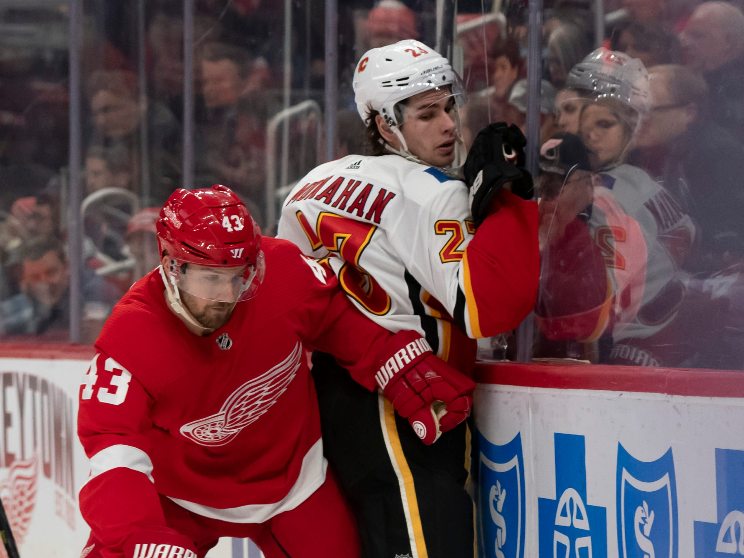 Detroit center Darren Helm checks Calgary center Sean Monahan in the first period.               Photos are of the Detroit Red Wings vs. the Calgary Flames, at Little Caesars Arena, in Detroit, January 2, 2019.  (David Guralnick / The Detroit News)