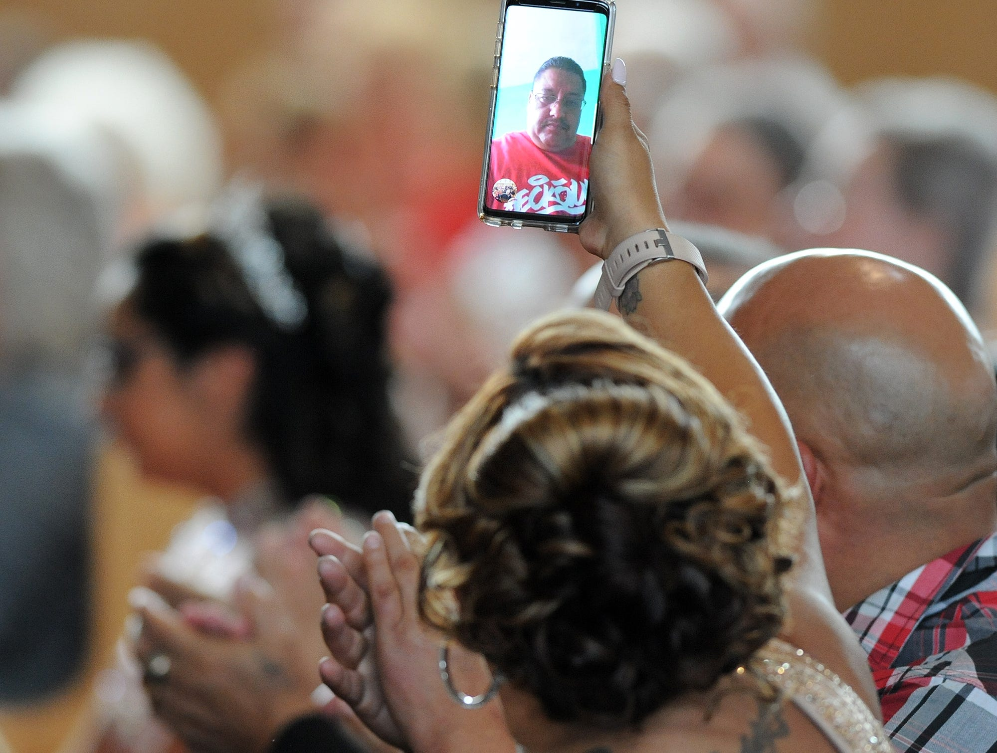 Cindy Garcia, holds up her cellphone, playing the Google Duo video calling app, so her husband, Jorge Garcia, to watch her quinceañera mass.