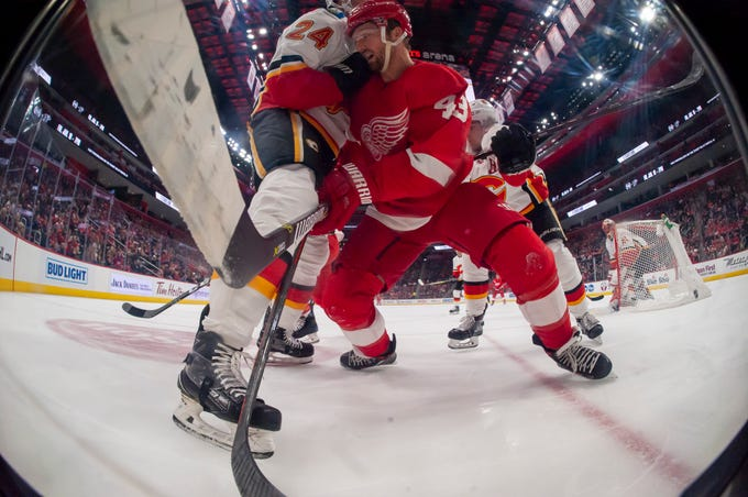 Detroit center Darren Helm and Calgary defenseman Travis Hamonic battle for position in the first period during the Flame's 5-3 win over the Red Wings at Little Caesars Arena, in Detroit, January 2, 2019.