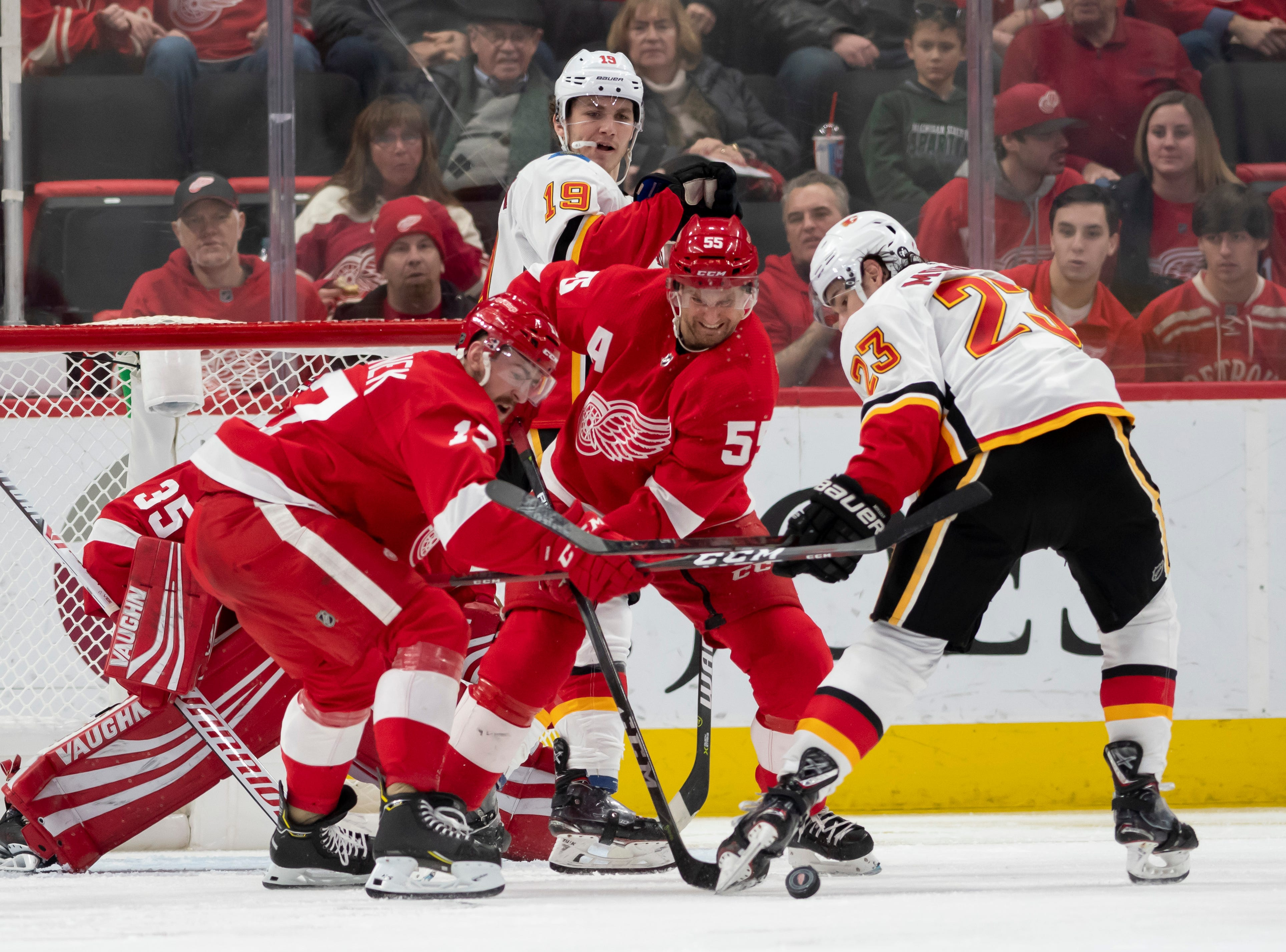 (From left) Detroit defenseman Filip Hronek, defenseman Niklas Kronwall, and Calgary center Sean Monahan battle for the puck in the third period.