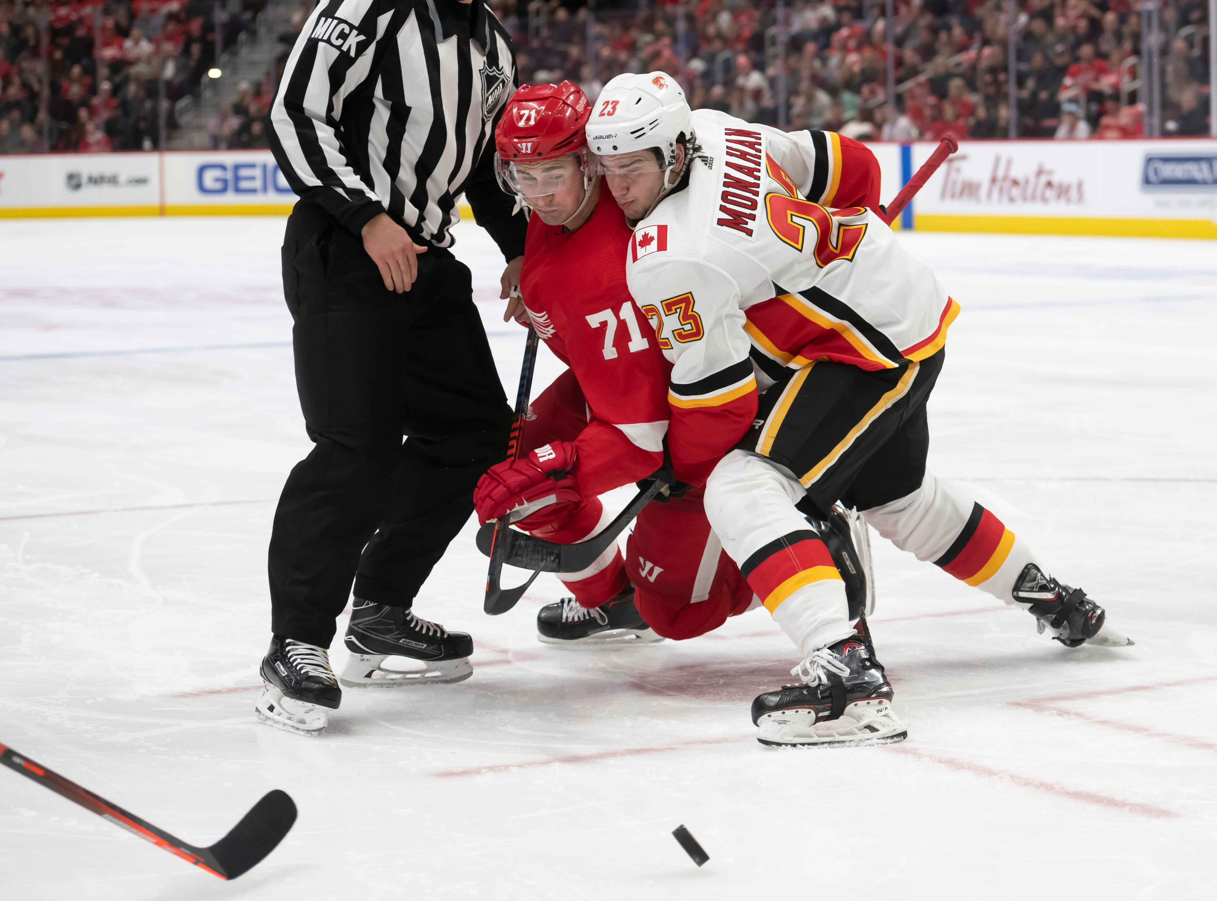 Detroit center Dylan Larkin and Calgary center Sean Monahan battle for a face-off in the third period.