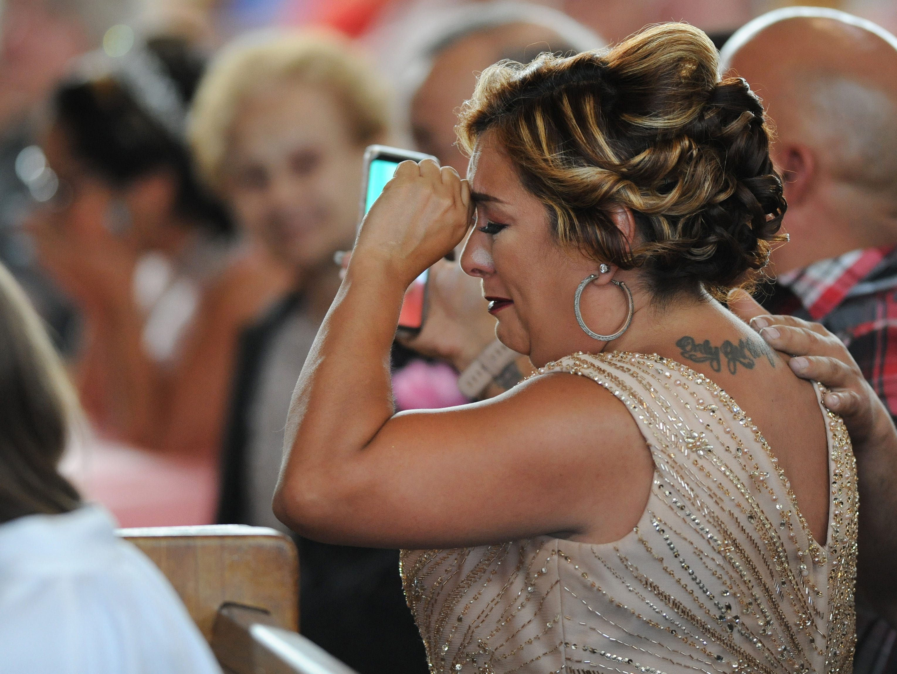 Cindy Garcia begins to cry after the priest acknowledges the absence of her husband, Jorge, at their daughter Soleil's quinceañera Mass in late July.