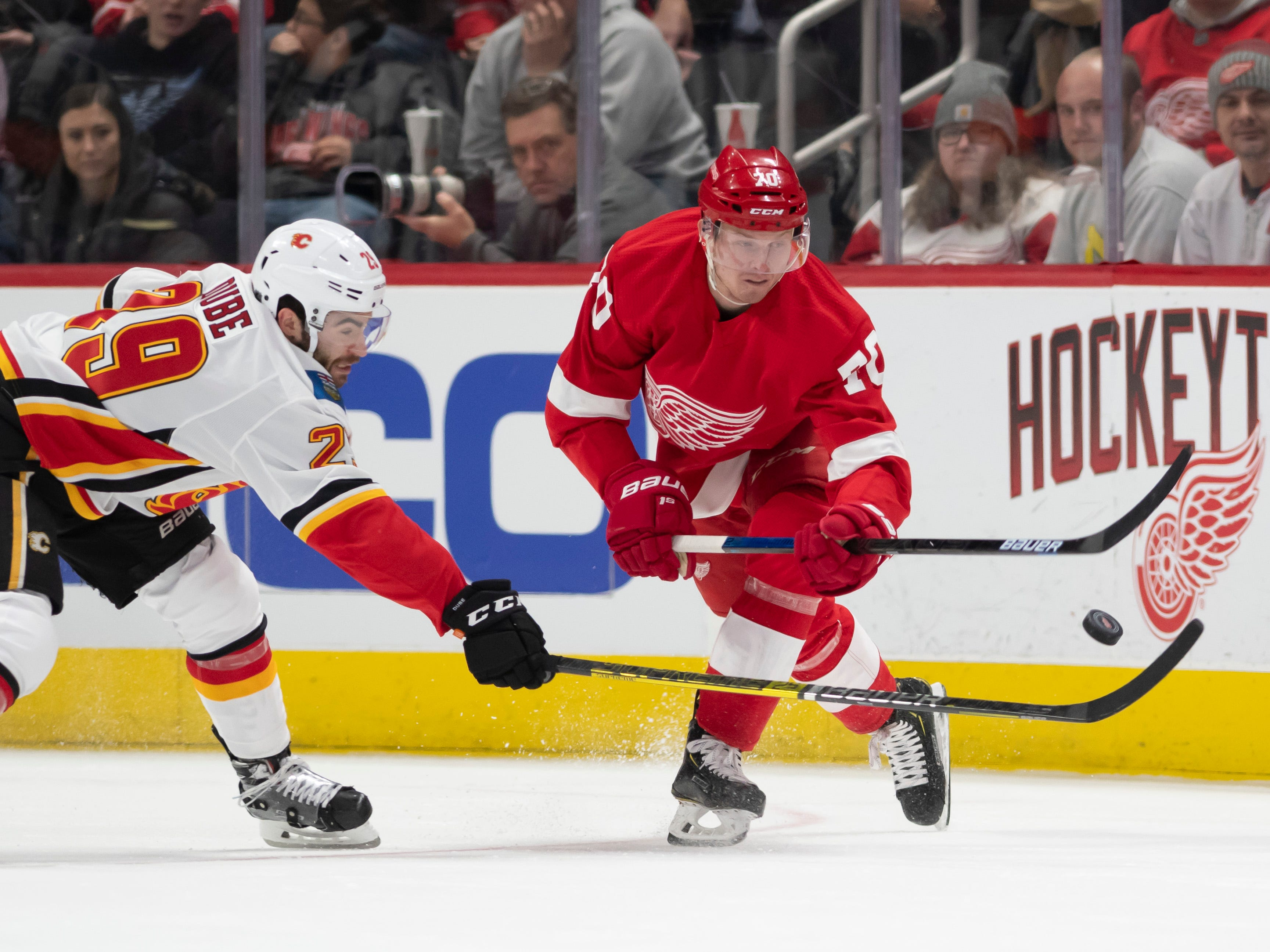 Calgary center Dillon Dube and Detroit center Christoffer Ehn battle for the puck in the first period.
