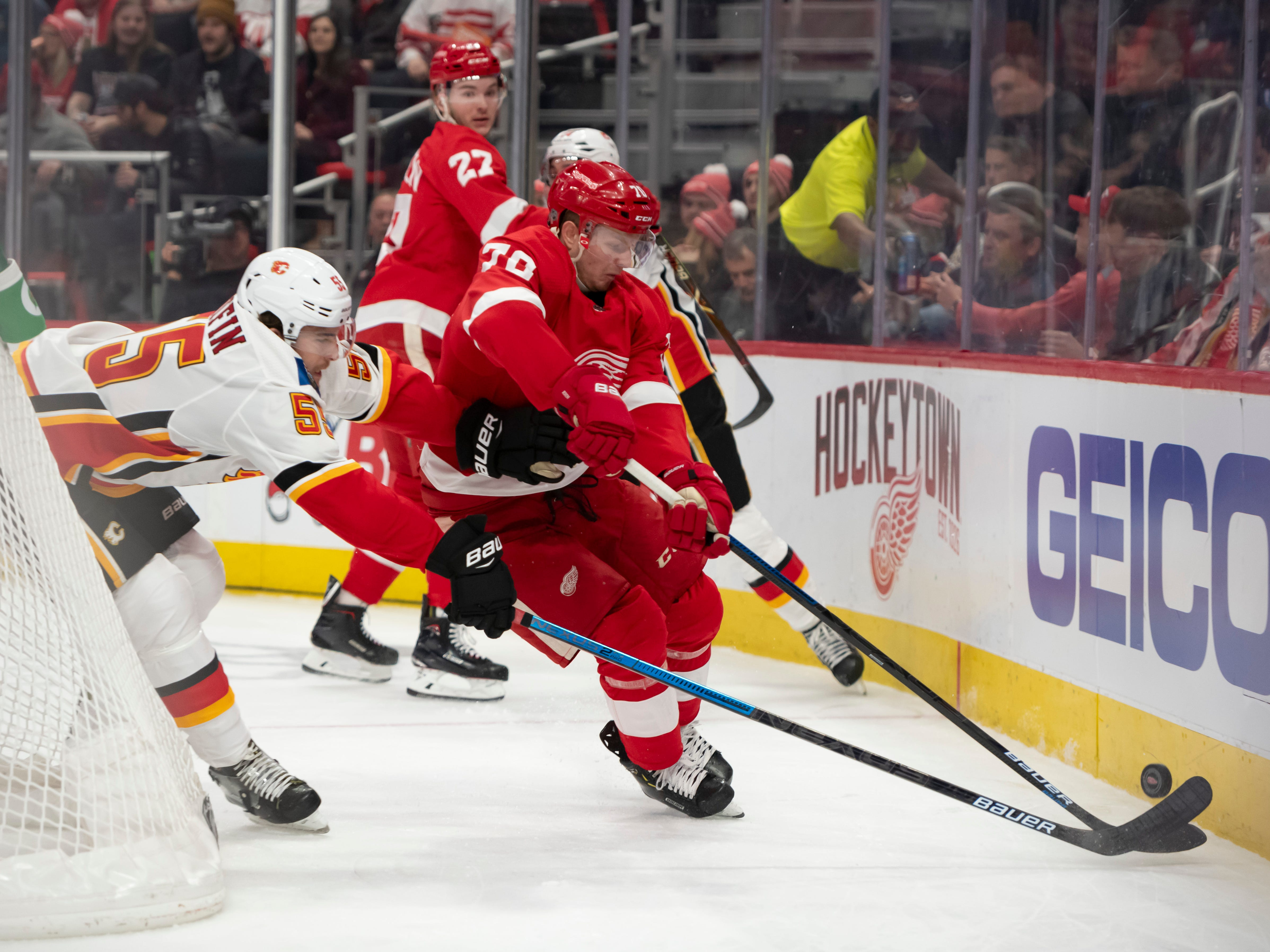 Detroit center Christoffer Ehn and Calgary defenseman Noah Hanifin battle for the puck in the first period.