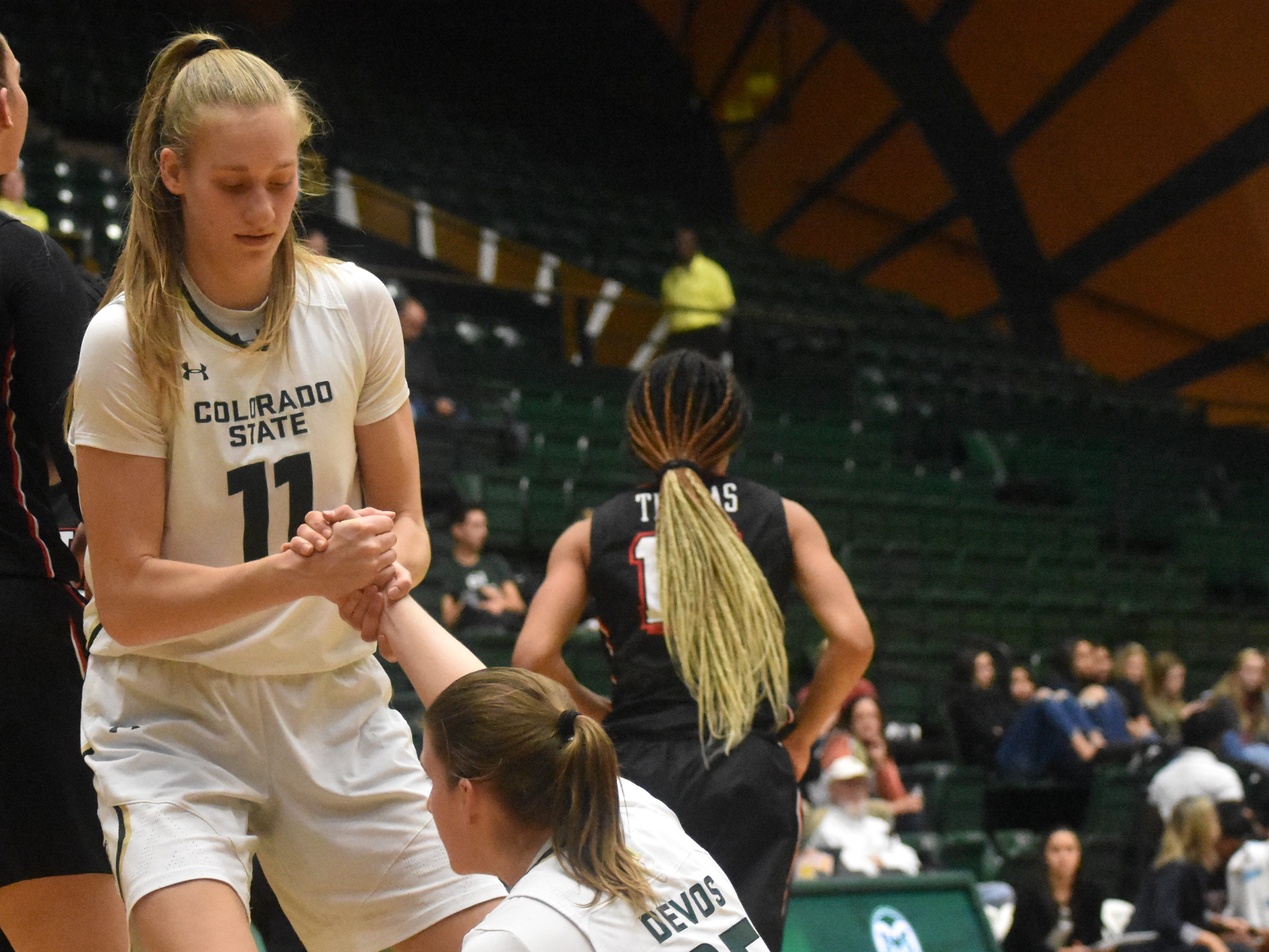 Colorado State basketball center Lena Svanholm helps up teammate Lore Devos during Wednesday's game against UNLV at Moby Arena.