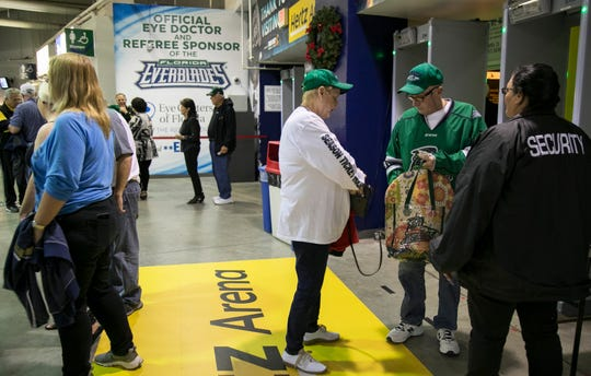 Pat Culp unloads items from her purse into a clear bag before returning her purse to her car Wednesday night at Hertz Arena. Only small purses are allowed under the new security policy at the arena.