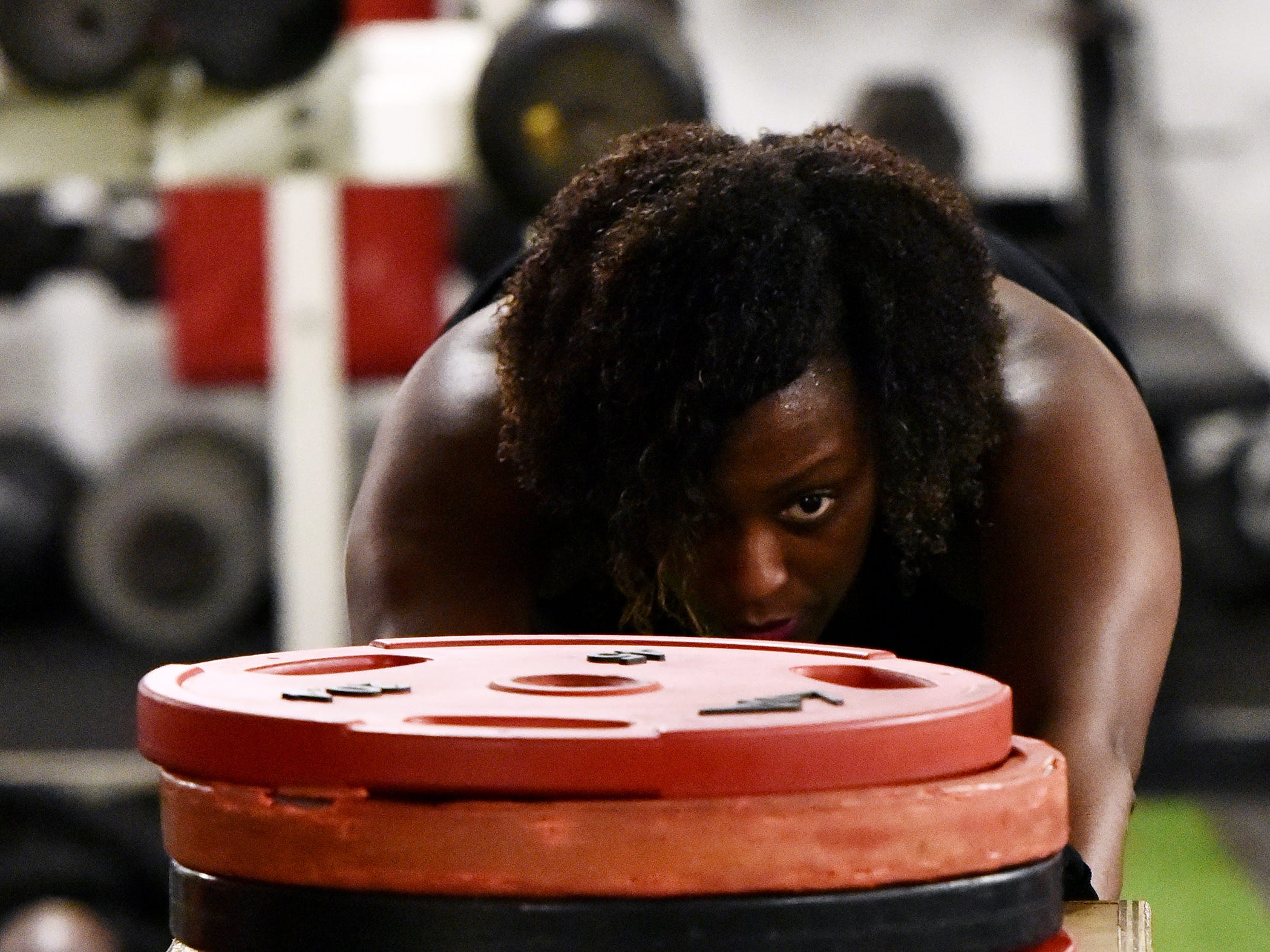 Jil Littlejohn pushes weights on a box during a work out at Brit's Brothers Gym in Greenville.