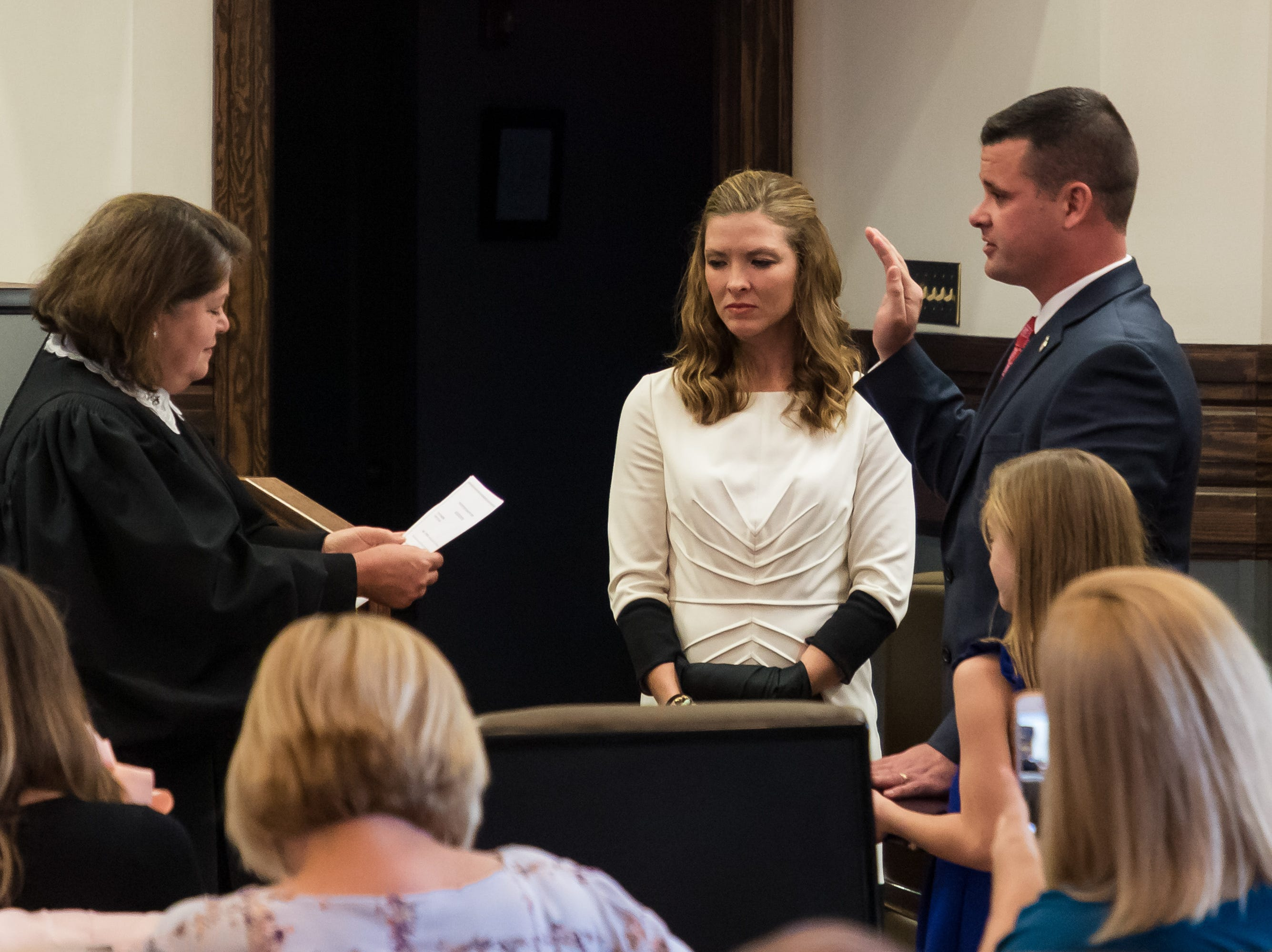 Justice Dawn Beam administers the oath of office to Lamar County and Youth Court Judge Brad Touchstone Wednesday, Jan. 2, 2019, as his wife, Janice, holds his robe, and his daughter Ryleigh, holds a Bible.