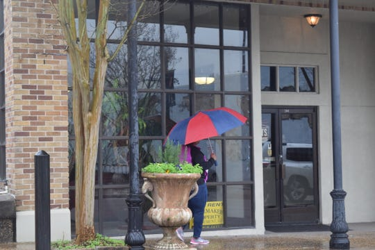 A pedestrian walks in the rain on Thursday, Jan. 3, 2019, on West Pine Street in Hattiesburg.