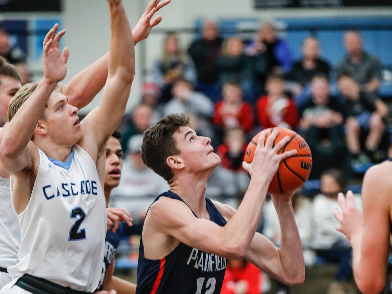 Plainfield High School's forward Ian Scott (13) shoots for the hoop during a 2019 Hendricks County Basketball Tournament game between Plainfield High School and Cascade High School, held at Cascade on Wednesday, Jan. 2, 2019. Cascade High School's A.J. Sanders (2), left.