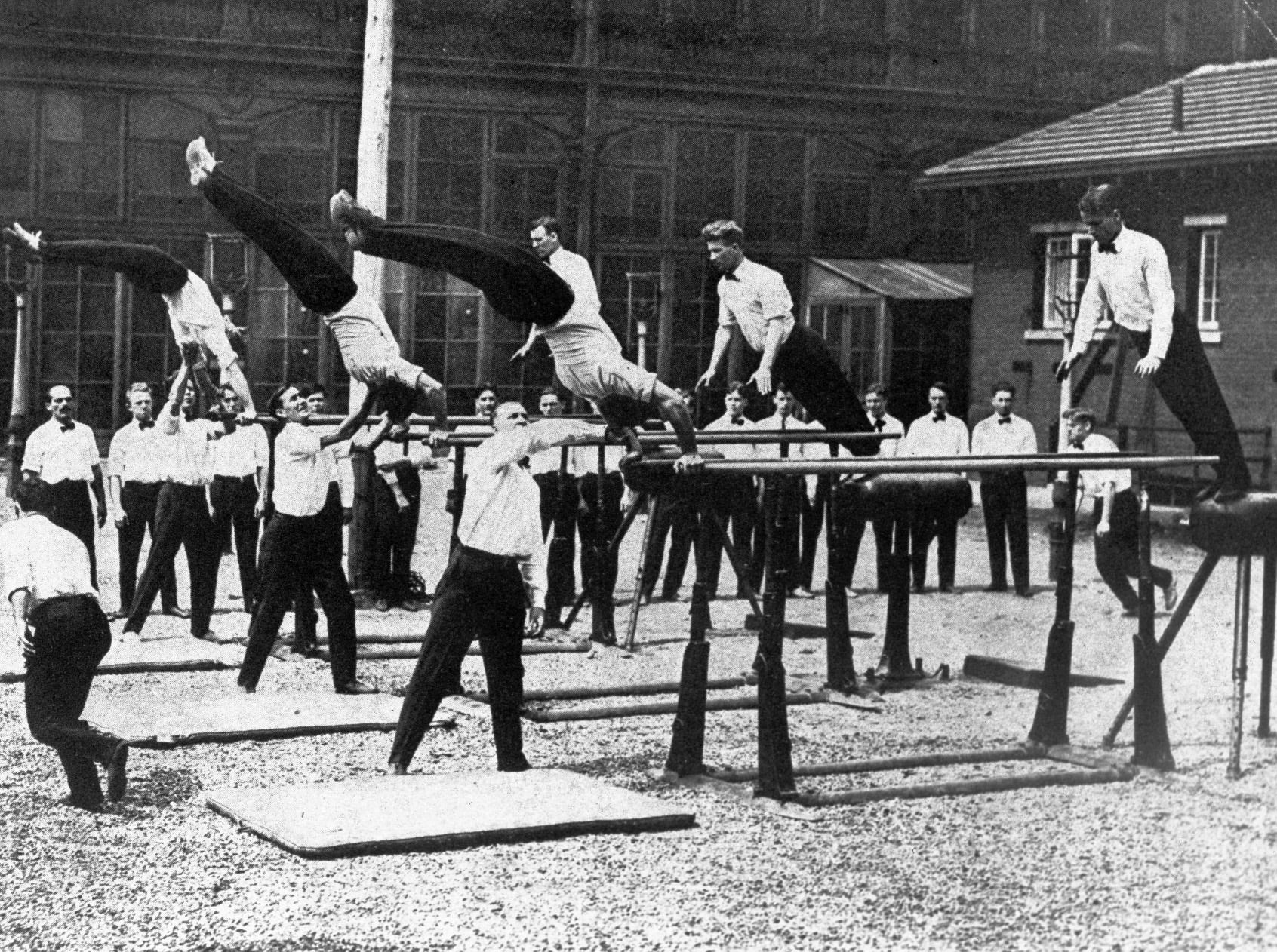 Men demonstrate use of the parallel bars at Normal College in the early 1900s (in what is now the beer garden at the Athenaeum). Normal College of the American Gymnastics Union was the collegiate training school of the North American Turnerbund.
