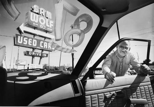 Ed Wolf looks into one of the used vehicles for sale at his late father's (Sam Wolf) used car lot in 1991.