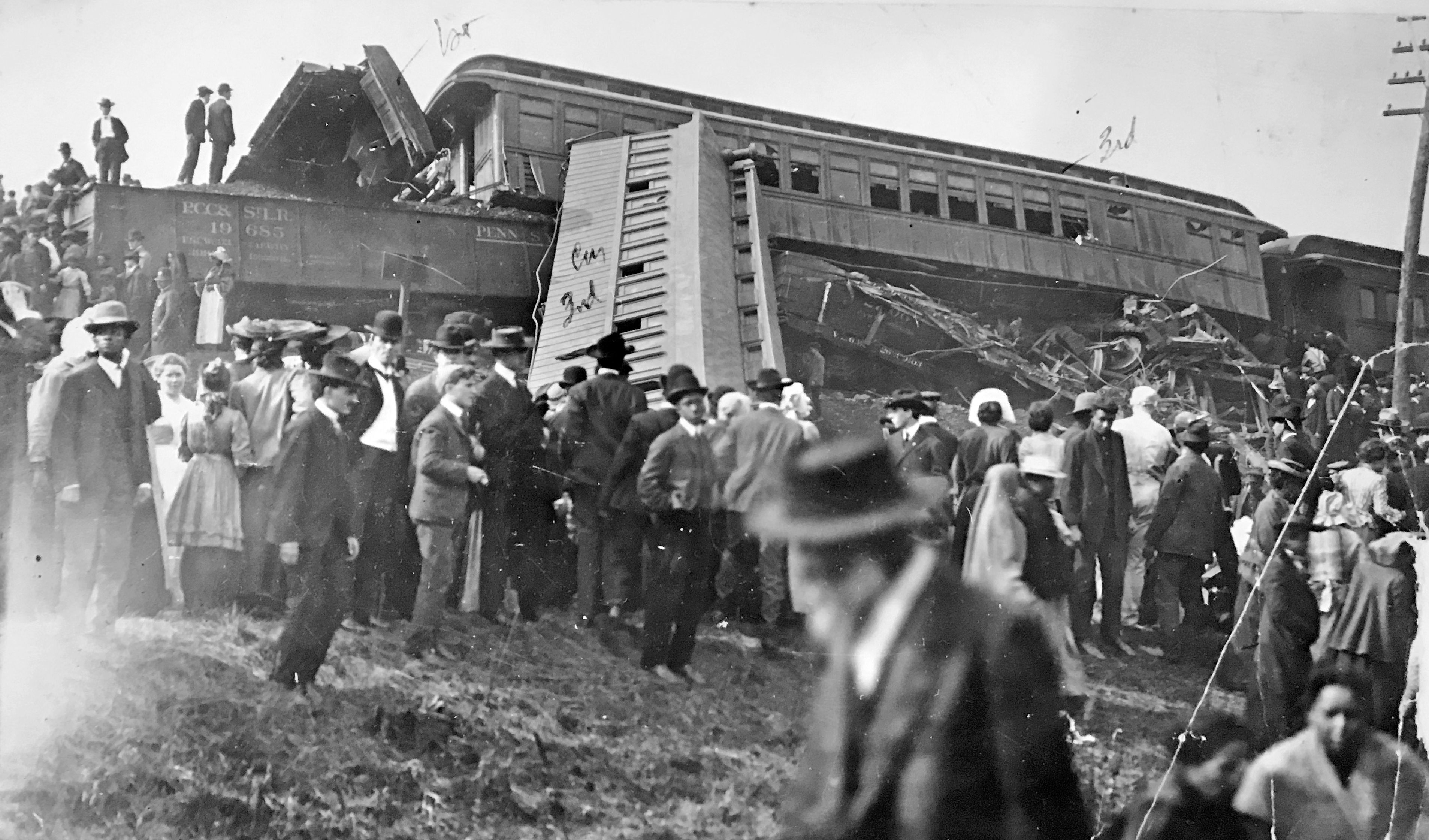 A scene from the wreckage of the train carrying the Purdue University football team in 1903. The team occupied the first car, resulting in the deaths of 13 players as well as an assistant coach and trainer. The second car (right) jumped the track and went down an embankment.