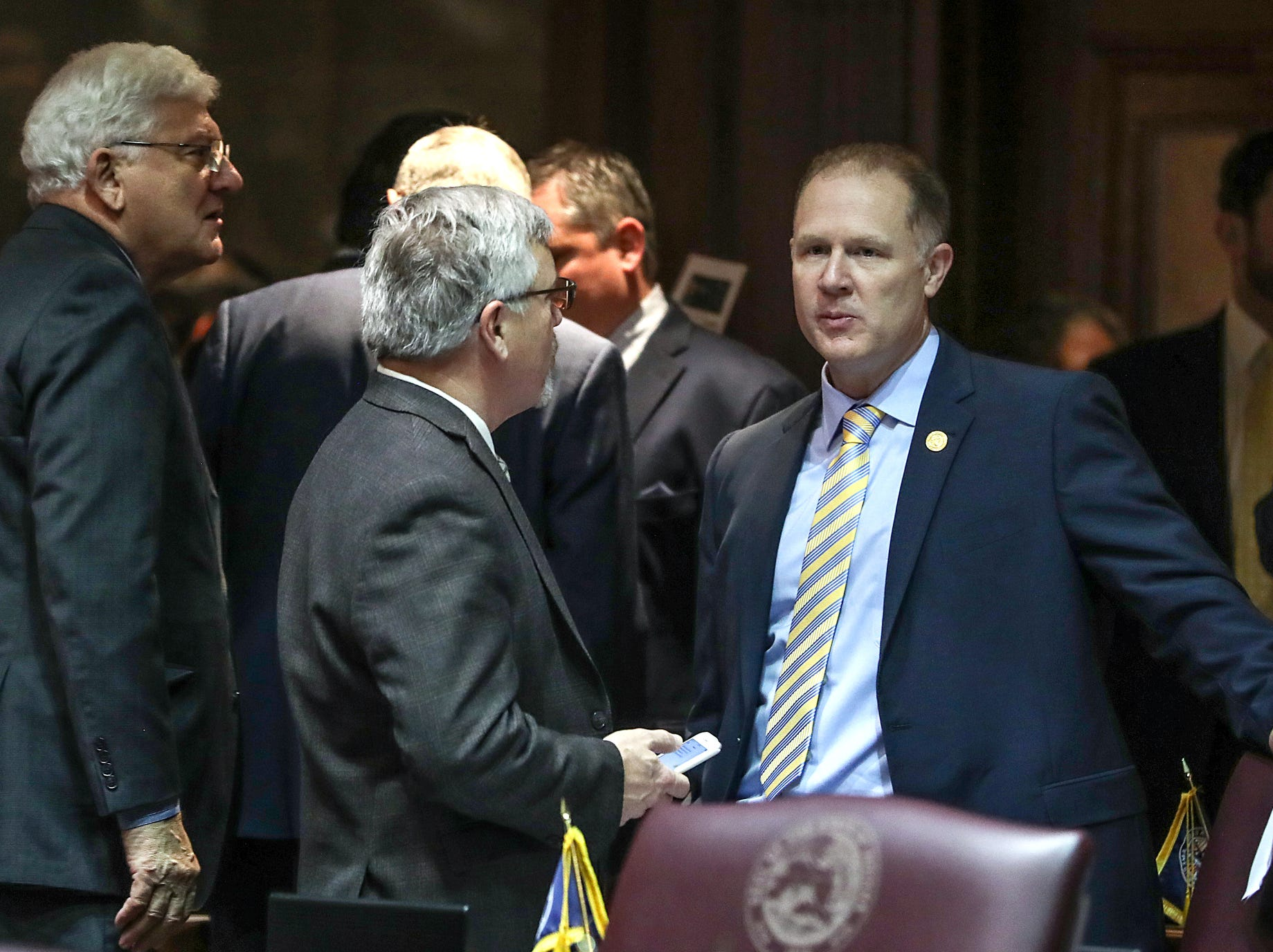 At right, Rep. Chris May talks with colleagues on the starting day of legislative session at the Indiana Statehouse, Indianapolis, Thursday, Jan. 3, 2019.