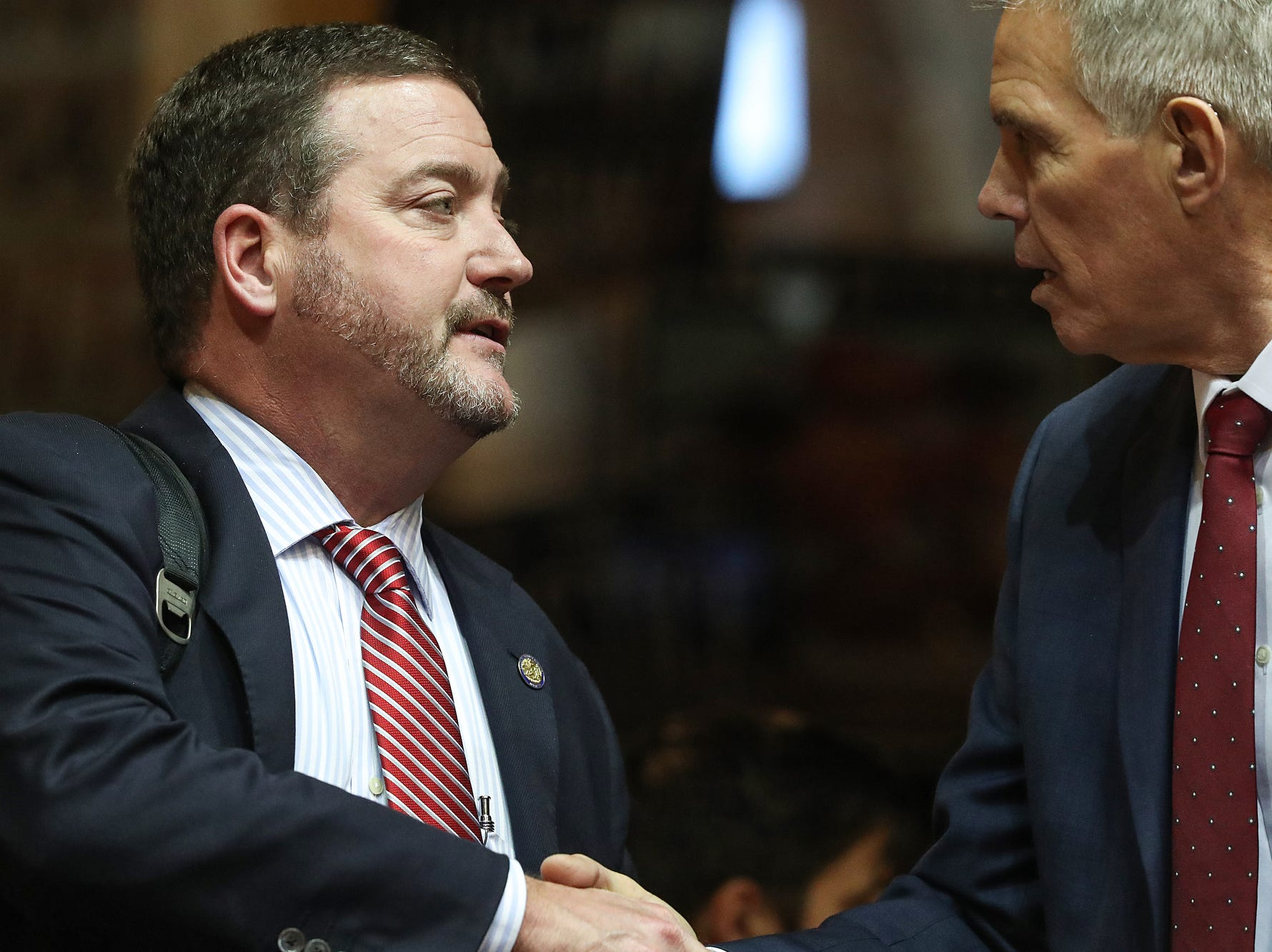 Rep. Chuck Goodrich shakes hand with Rep. David Abbott on the starting day of legislative session at the Indiana Statehouse, Indianapolis, Thursday, Jan. 3, 2019.