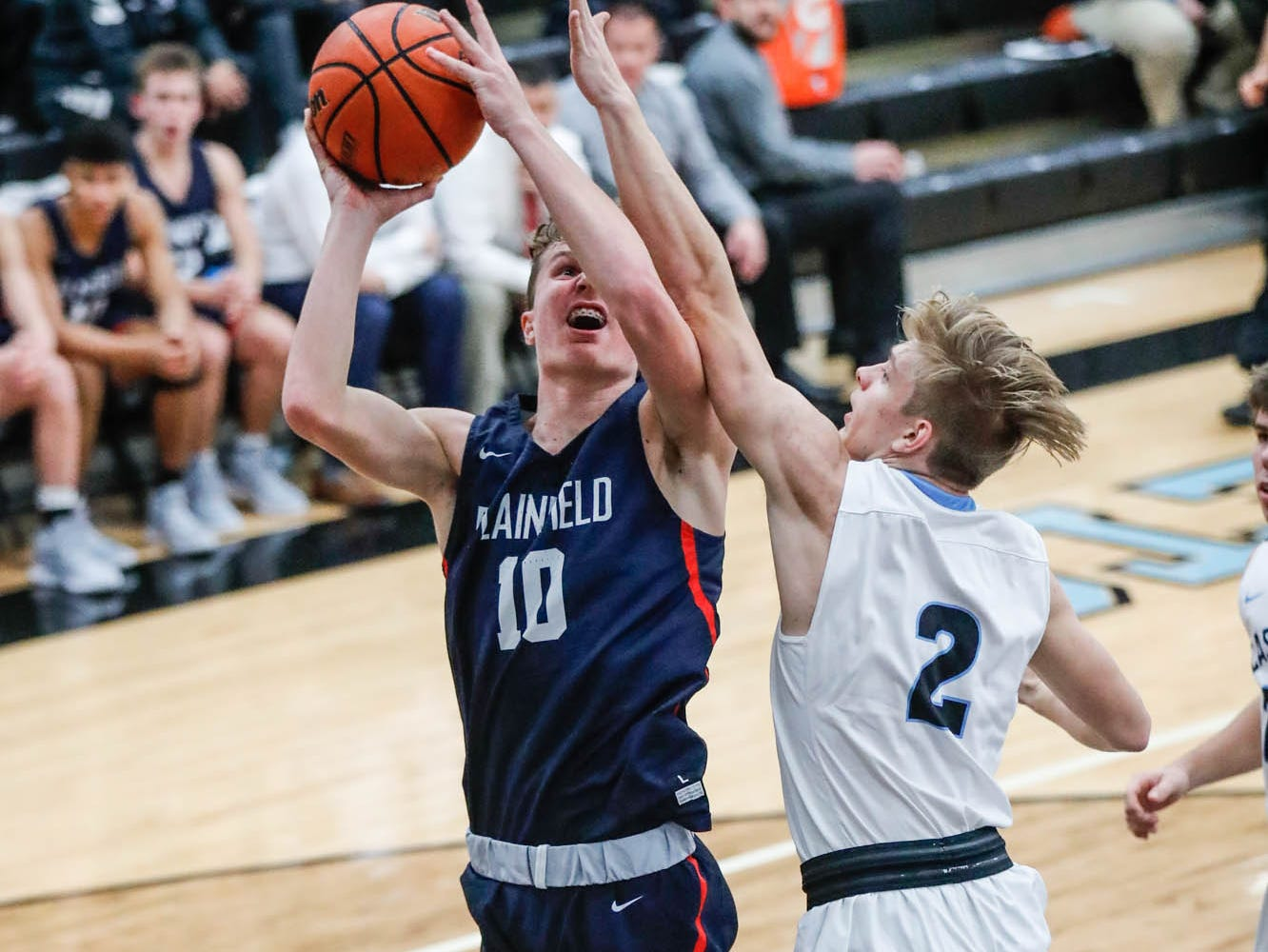 Plainfield High School's forward Cade East (10), attempts a shot around Cascade High School's A.J. Sanders (2), during a 2019 Hendricks County Basketball Tournament game between Plainfield High School and Cascade High School, held at Cascade on Wednesday, Jan. 2, 2019.