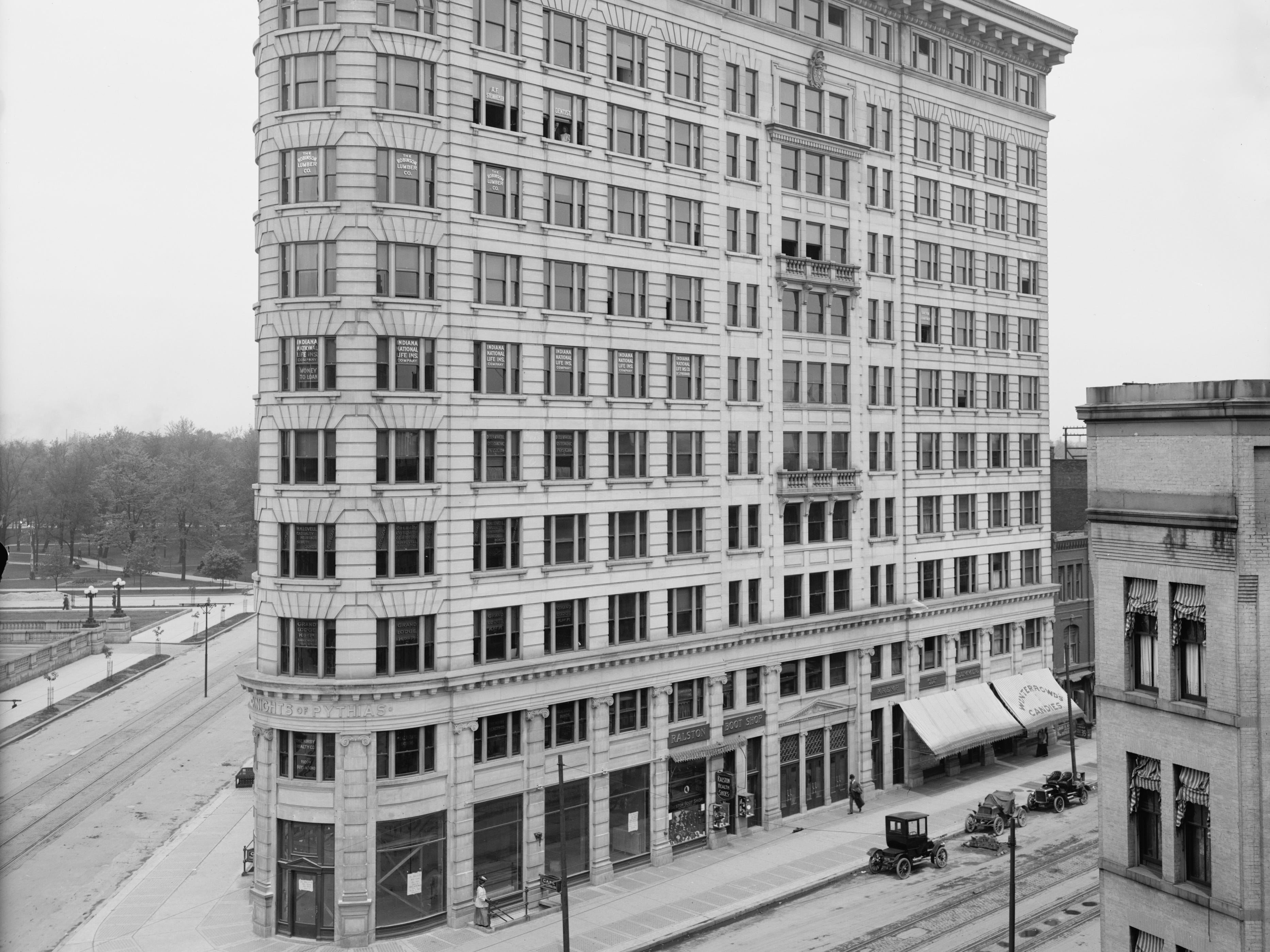 "This was the Knights of Pythias building circa 1906 and newly constructed. That's Pennsylviania Street on the left and Massachusetts Ave. on the right.  The building's ""flatiron"" design was one of several in Indianapolis at the time. The ""K of P"" building was torn down in 1967 and this section of Massachusetts was eliminated so that the entire block could be used for the new Indiana National bank tower (later to become Regions Bank)."