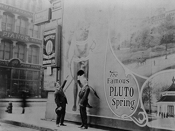 "Harry Houdini and unidentified man pose before advertising posters in Indianapolis, Indiana ""Houdini was in Indianapolis from December 29, 1907 to January 4, 1908. Time enough to enjoy his own image presented between an advertisement for The Terre Haute (Ind.) Brewing Co. and one for The Famous Pluto Spring."""
