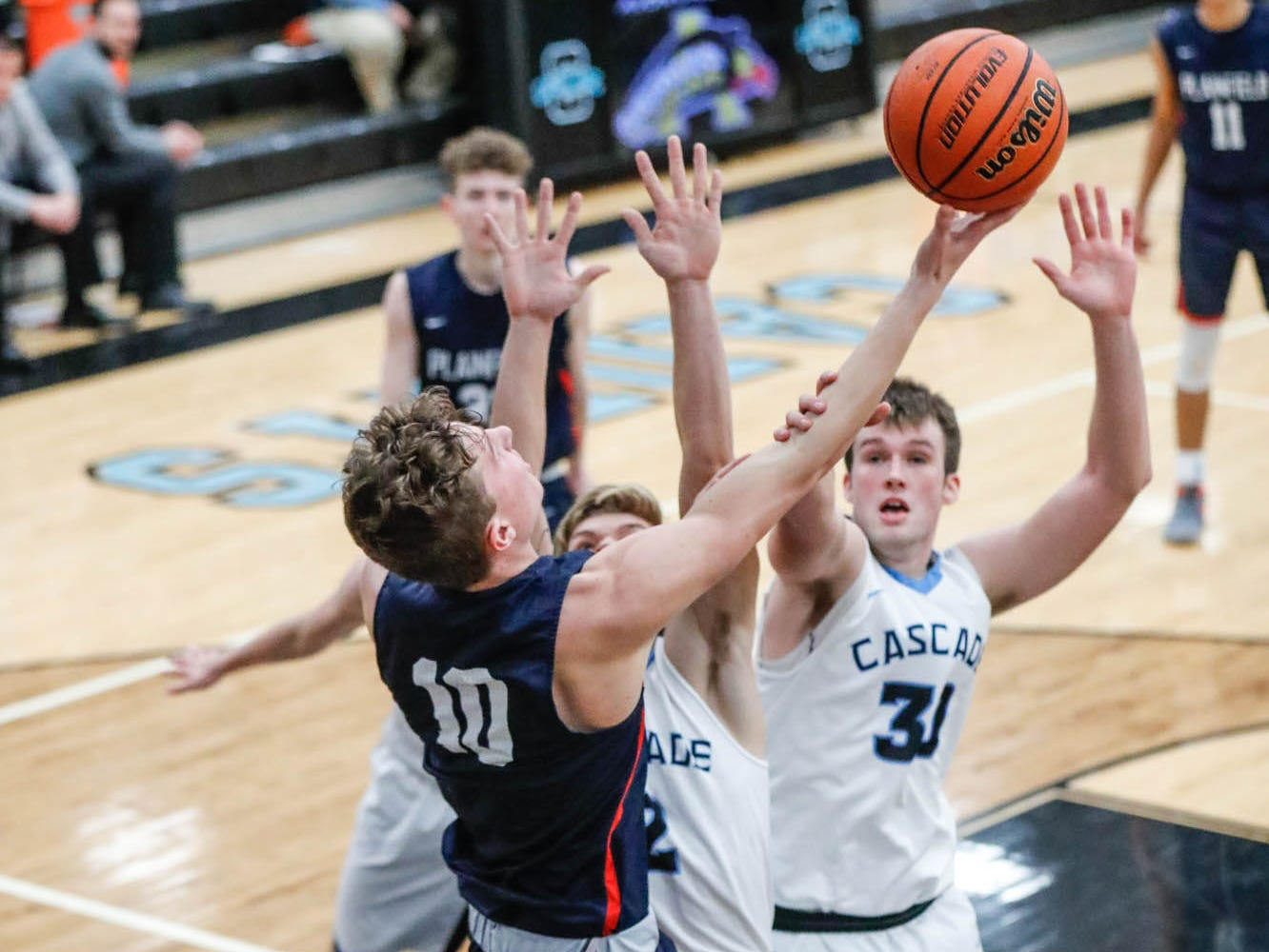 Plainfield High School's forward Cade East (10), attempts a hook shot around Cascade High School's Benson Walker (30), and Cascade High School's A.J. Sanders (2), during a 2019 Hendricks County Basketball Tournament game between Plainfield High School and Cascade High School, held at Cascade on Wednesday, Jan. 2, 2019.