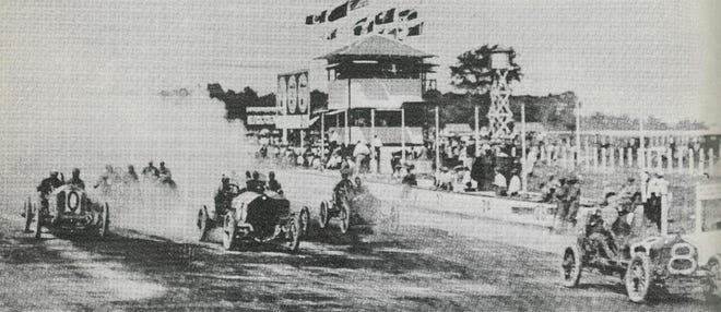 Johnny Aitken in National Car 8 grabs an early lead in the 10-Mile Race at the Indianapolis Motor Speedway August 19, 1909.