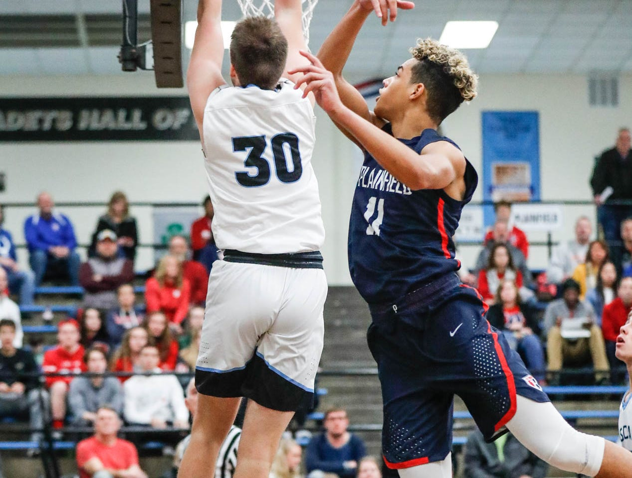 Cascade High School's Benson Walker (30), and Plainfield High School's forward Cade Gibbs (11) jump for a rebound during a 2019 Hendricks County Basketball Tournament game between Plainfield High School and Cascade High School, held at Cascade on Wednesday, Jan. 2, 2019.