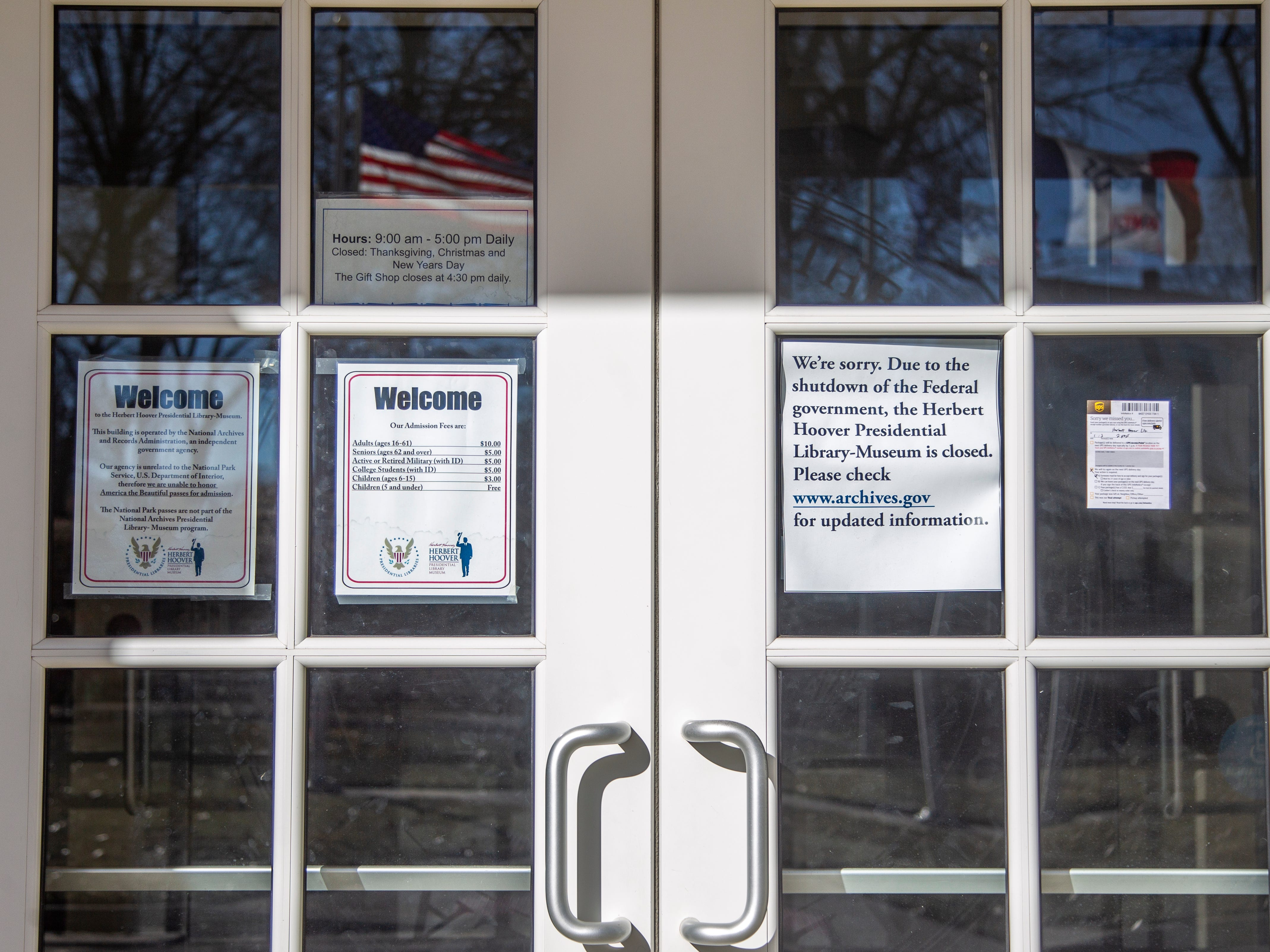 Welcome signs hang opposite a piece of paper notifying guests about the government shutdown on Thursday, Jan. 3, 2019, at the Herbert Hoover Presidential Library-Museum in West Branch, Iowa.