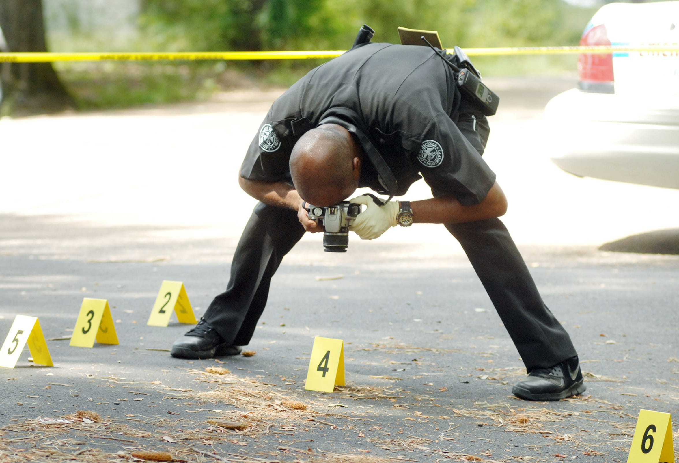 A crime scene investigator photographs shell casings.