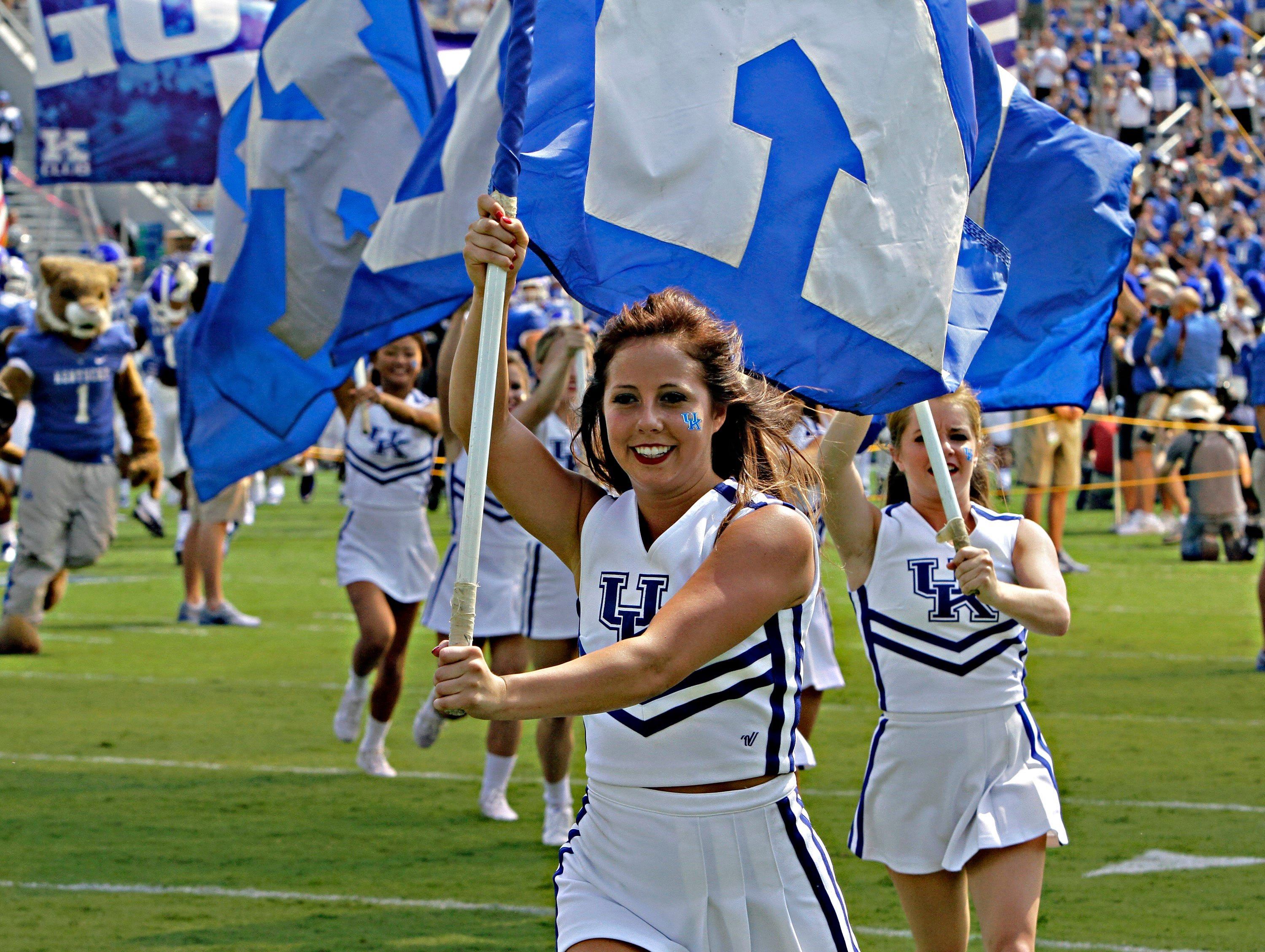 University of Kentucky cheerleaders lead the football team on to the field at Commonwealth Stadium before the start of a NCAA college football game against Tennessee-Martin in Lexington, Ky., Saturday, Aug. 30, 2014. (AP Photo/Garry Jones)