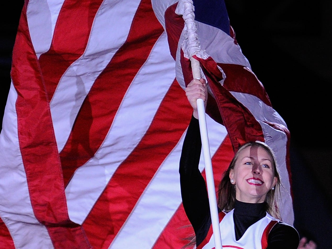A Georgia cheerleader runs onto the court with an American flag during the first half of an NCAA college basketball game between Georgia and Mississippi State on Thursday, Jan. 21, 2016, in Athens, Ga. (AP Photo/AJ Reynolds)