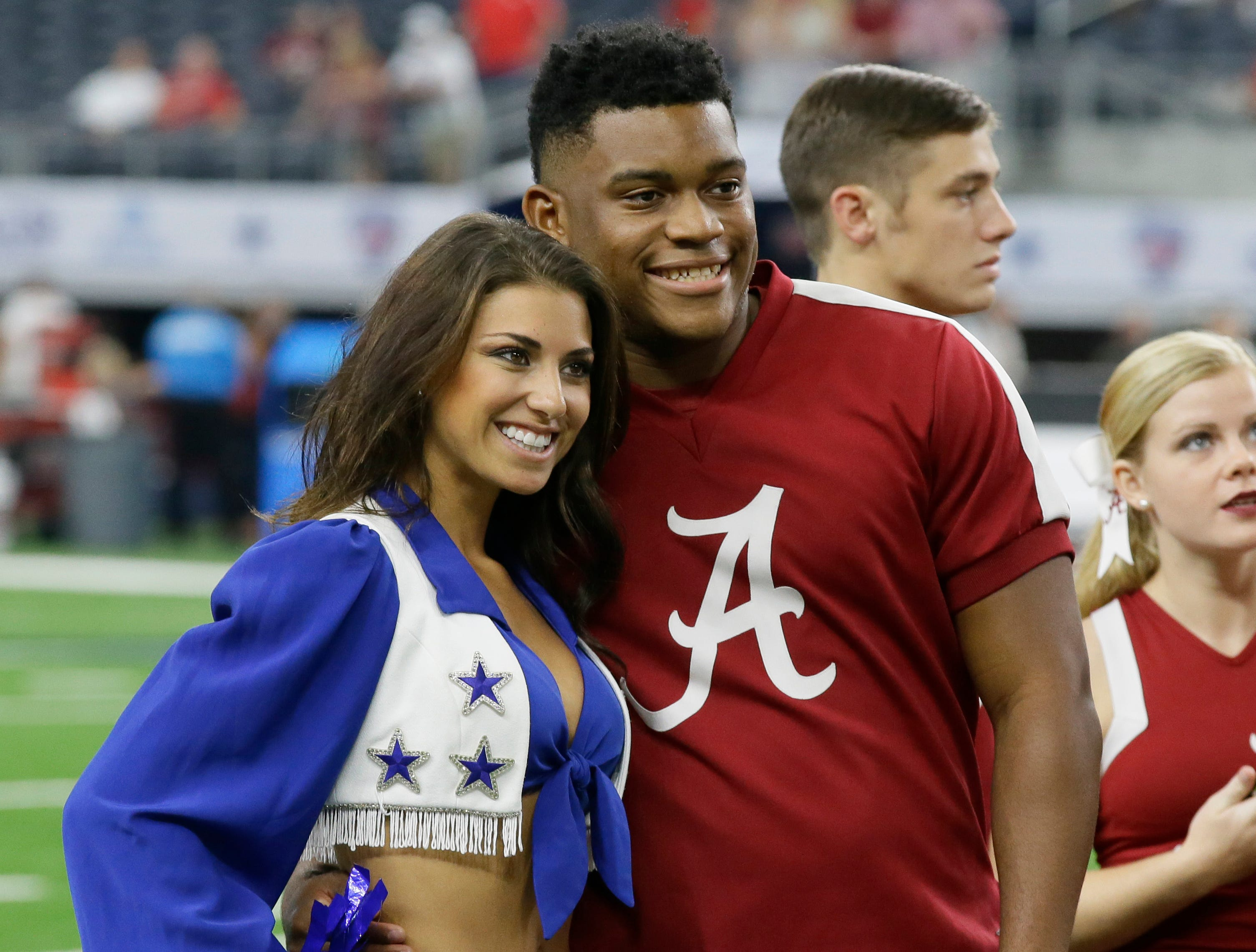 An Alabama cheerleader poses for a photo with Dallas Cowboys cheerleader before an NCAA college football game between Wisconsin and Alabama, Saturday, Sept. 5, 2015, in Arlington, Texas. (AP Photo/LM Otero)