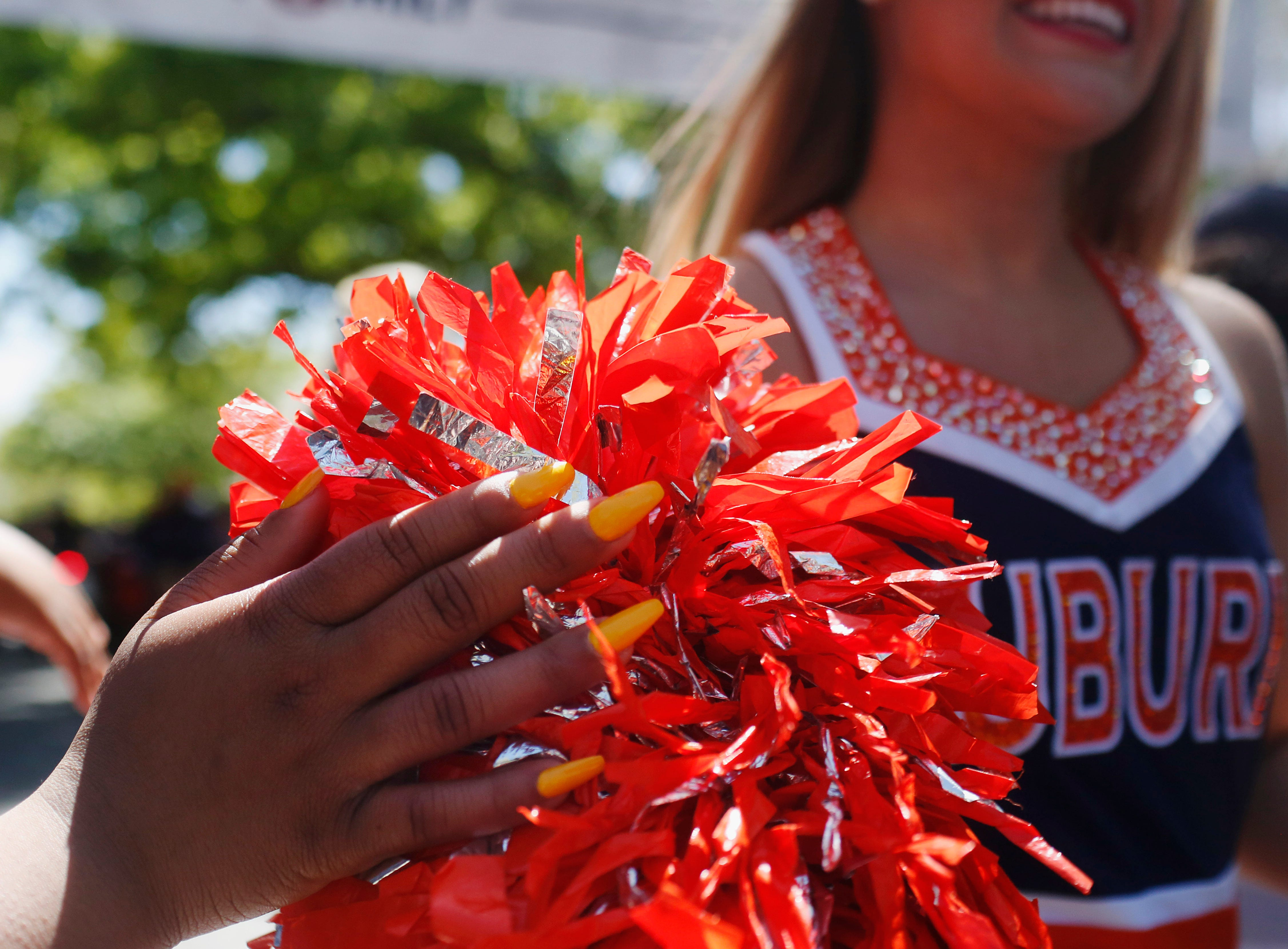 An Auburn fan with long orange nails high fives cheerleaders during the tiger walk before an NCAA college football game Saturday, April 9, 2016, in Auburn, Ala. (AP Photo/Brynn Anderson)