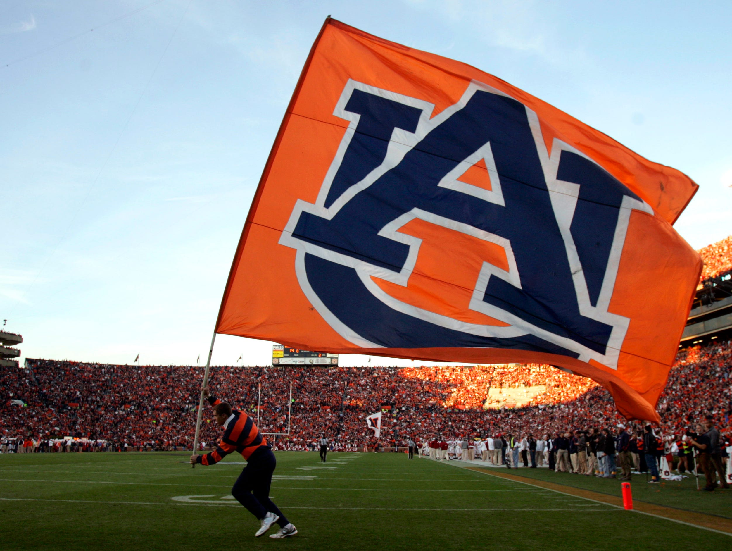 An Auburn cheerleader waves the Auburn flag after a touchdown during the second half of an NCAA college football game on Saturday, Nov. 30, 2013, in Auburn, Ala. (AP Photo/Butch Dill)