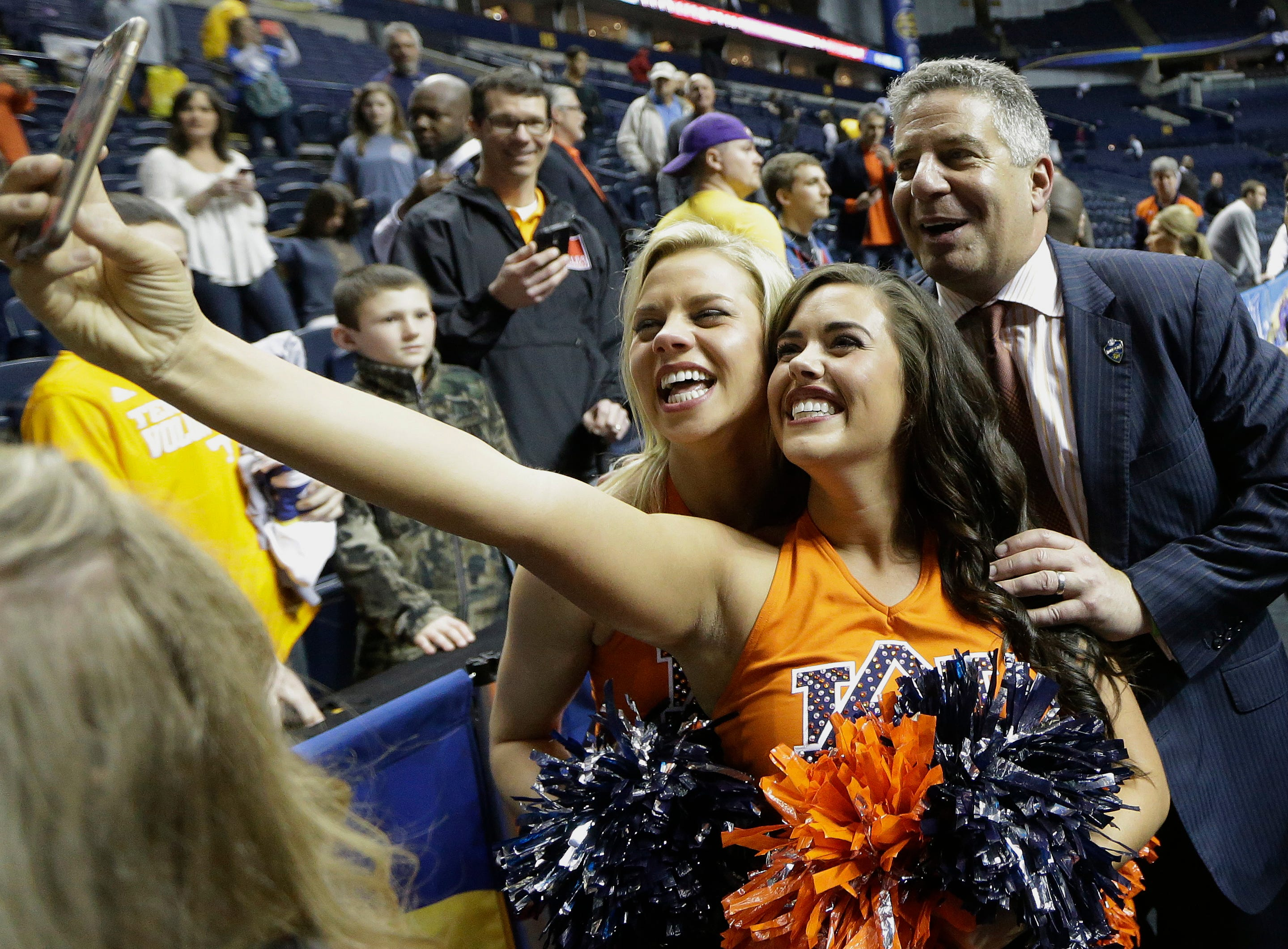 Auburn head coach Bruce Pearl steps into a photo made by Auburn cheerleaders after overtime of an NCAA college basketball game in the quarterfinal round of the Southeastern Conference tournament against LSU, Friday, March 13, 2015, in Nashville, Tenn. Auburn won in overtime 73-70. (AP Photo/Mark Humphrey)