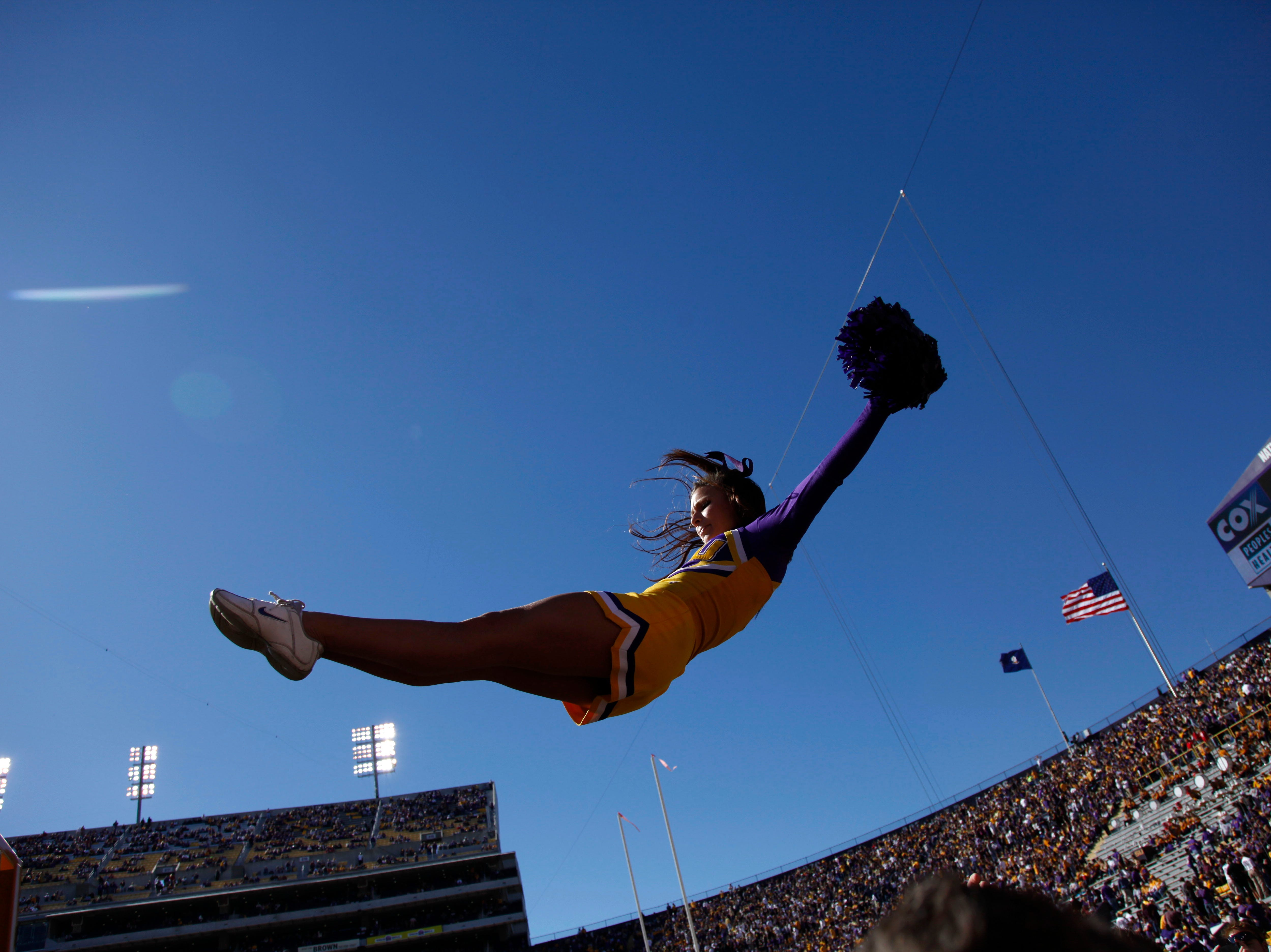 An LSU cheerleader leaps from the truck carrying Mike the TIger mascot, a live bengal tiger, prior to their NCAA college football game against Alabama in Baton Rouge, La., Saturday, Nov. 6, 2010. (AP Photo/Gerald Herbert)