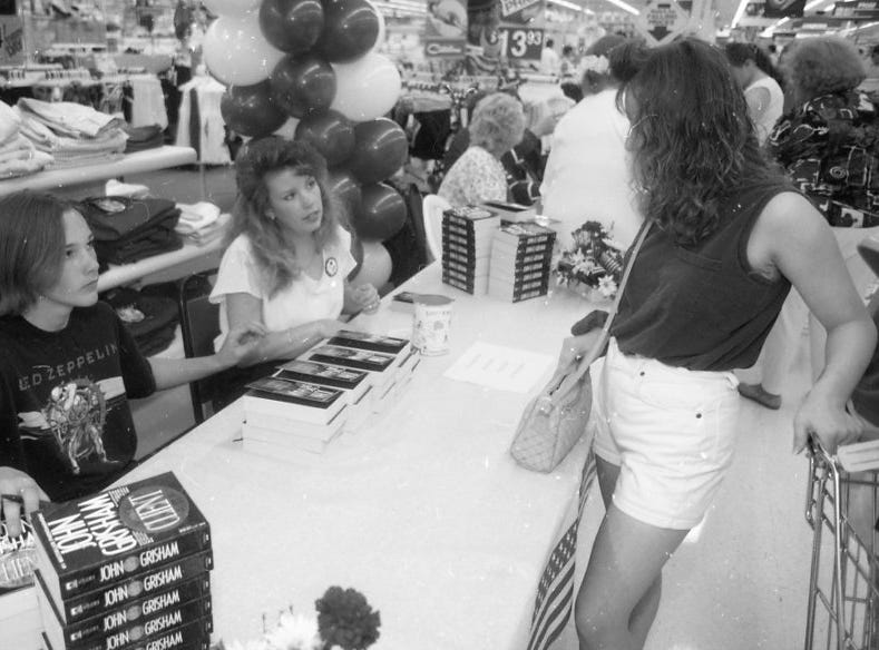 "Brad Renfro, a local actor who starred in the movie ""The Client"", at left, prepares to autograph a book for Tammy Riseden of Powell, right, as Wal-Mart employee Amy Tidler, center, looks on. Renfro was on hand for the store's re-grand opening activities Tuesday."